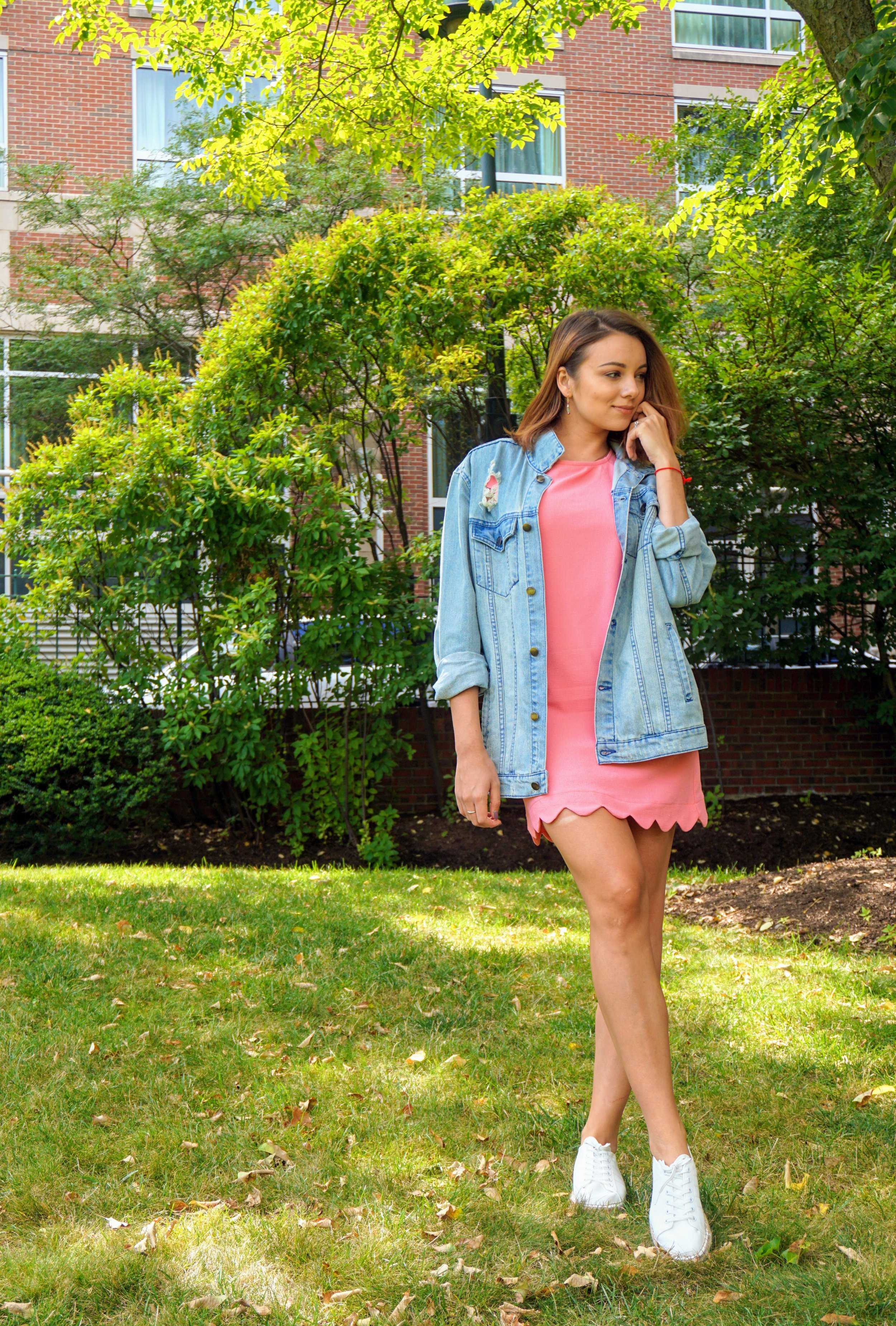A fashion blogger wearing a pink dress, oversized denim jacket, and white sneakers.