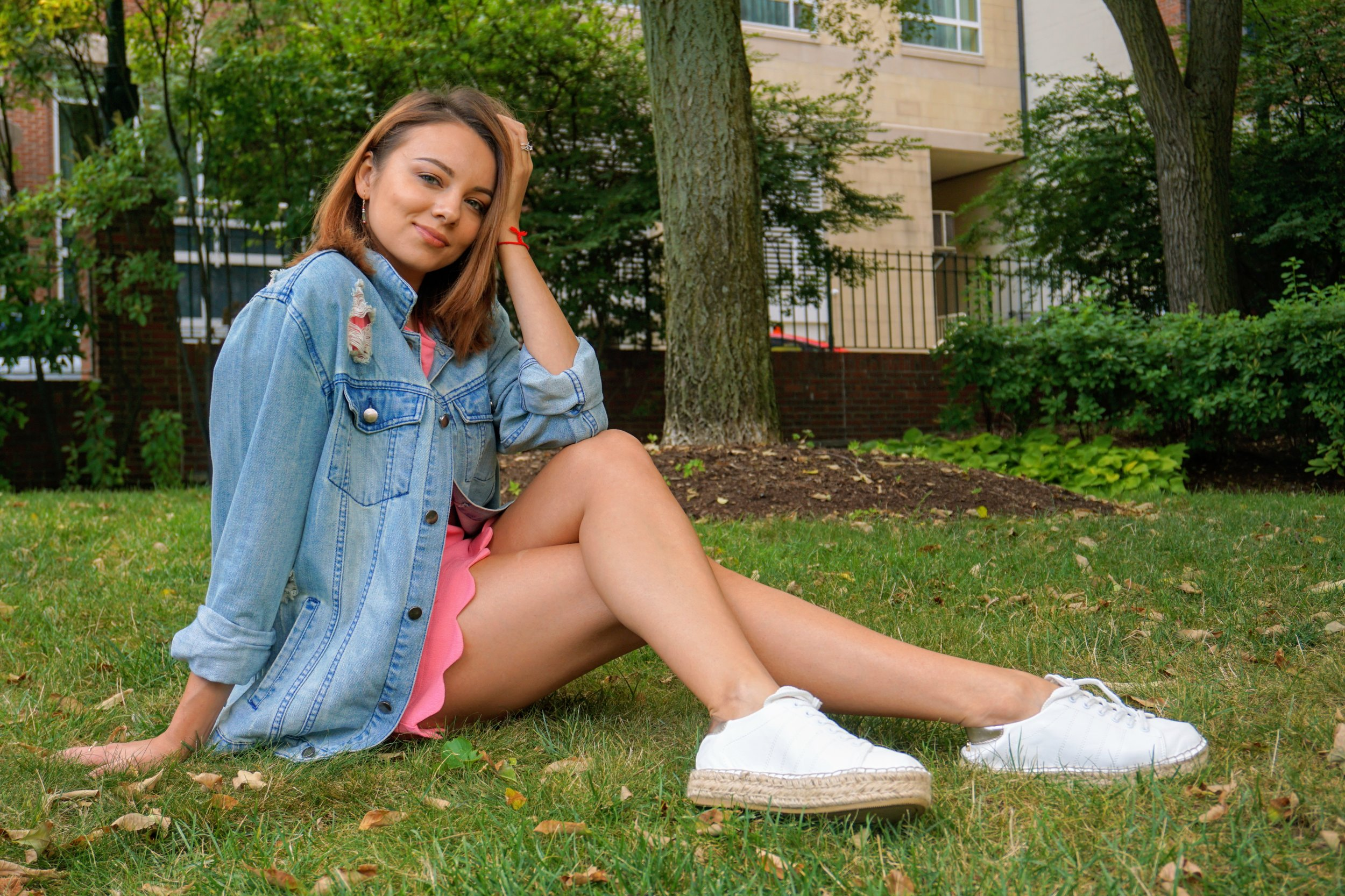A fashion blogger sitting on the grass, wearing a pink short dress, blue denim oversized jacket and white sneakers.