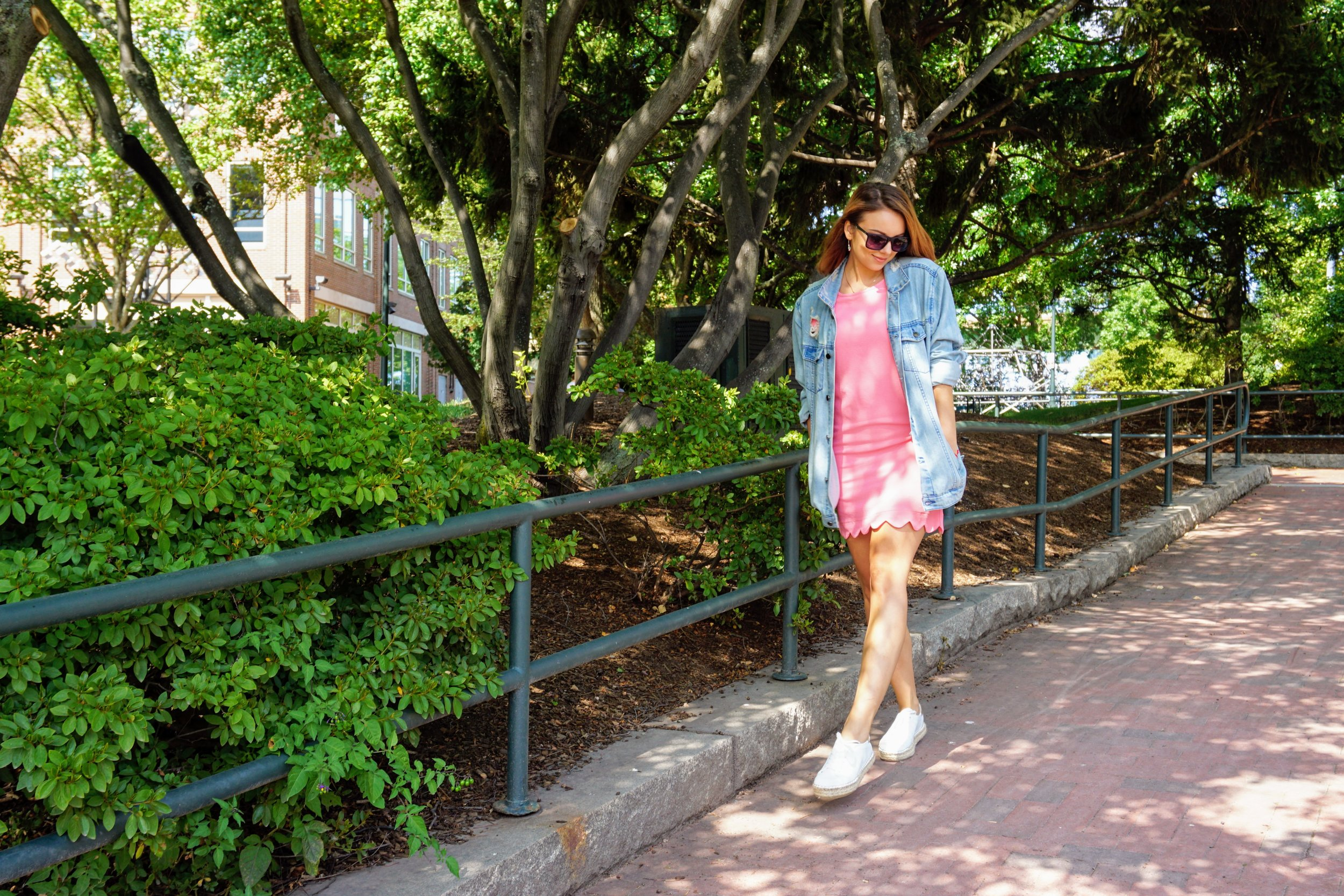 A style blogger wearing a casual look: pink dress, oversized denim jacket, and white sneakers.