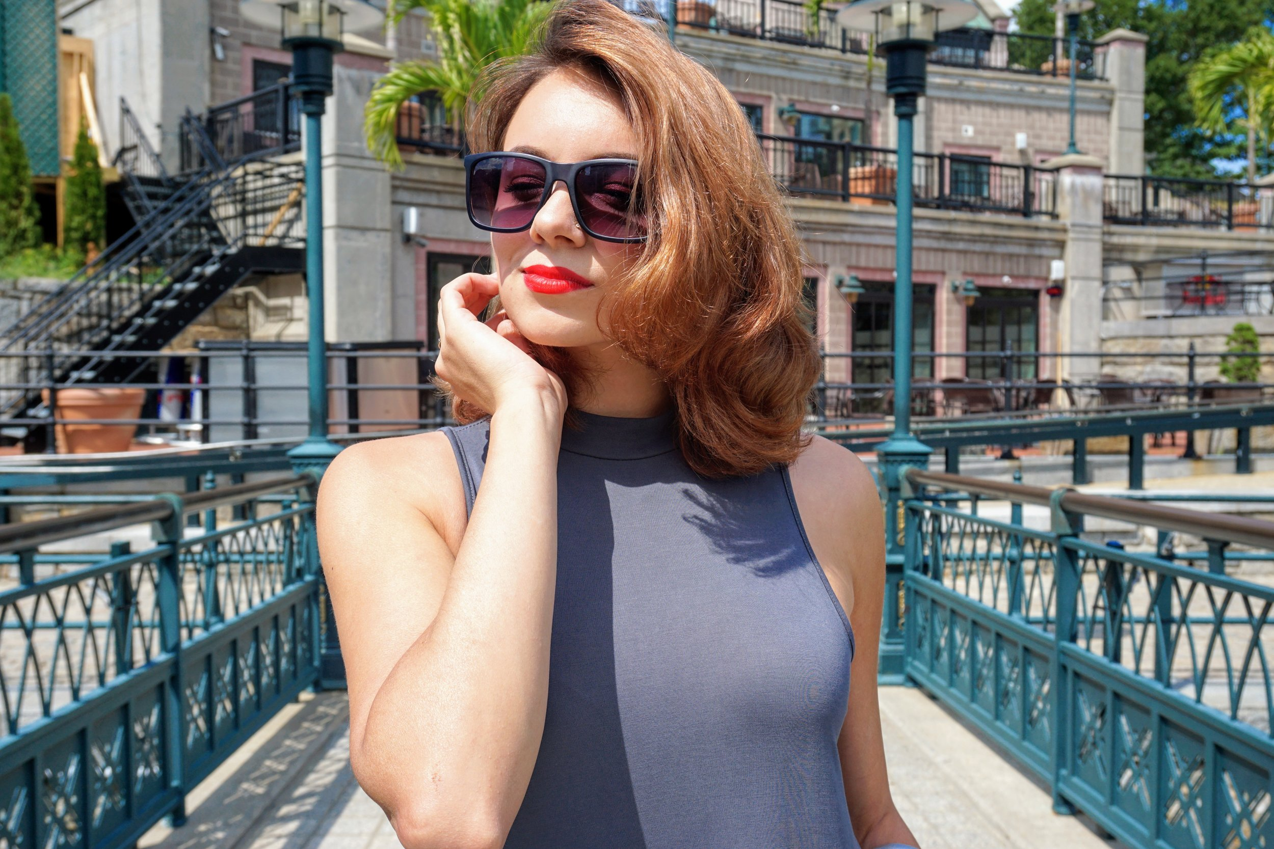 A close up of a blogger: red lips, short wavy hair, gray dress.