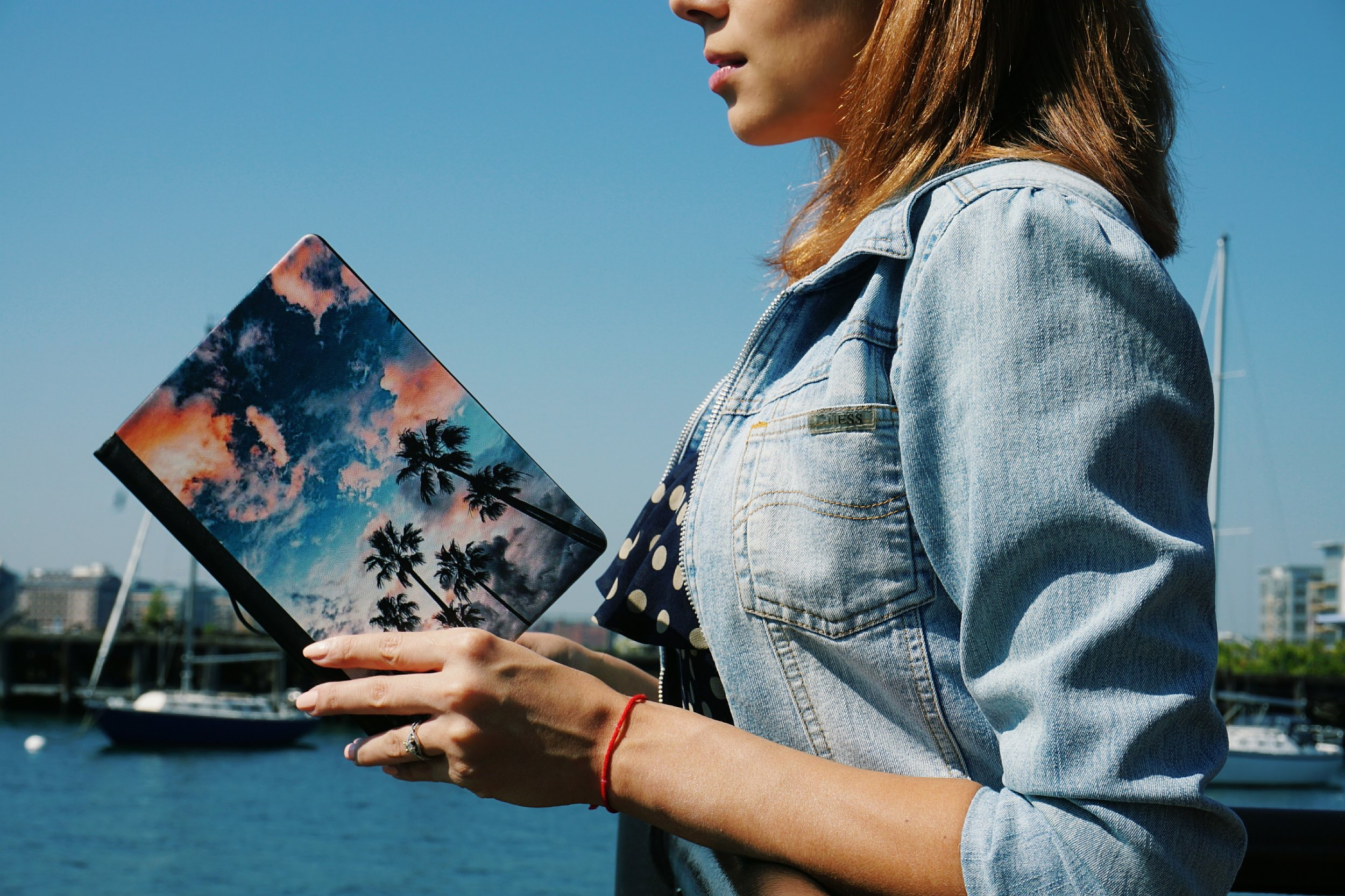 A blogger holding a notebook with a customized photo on it.