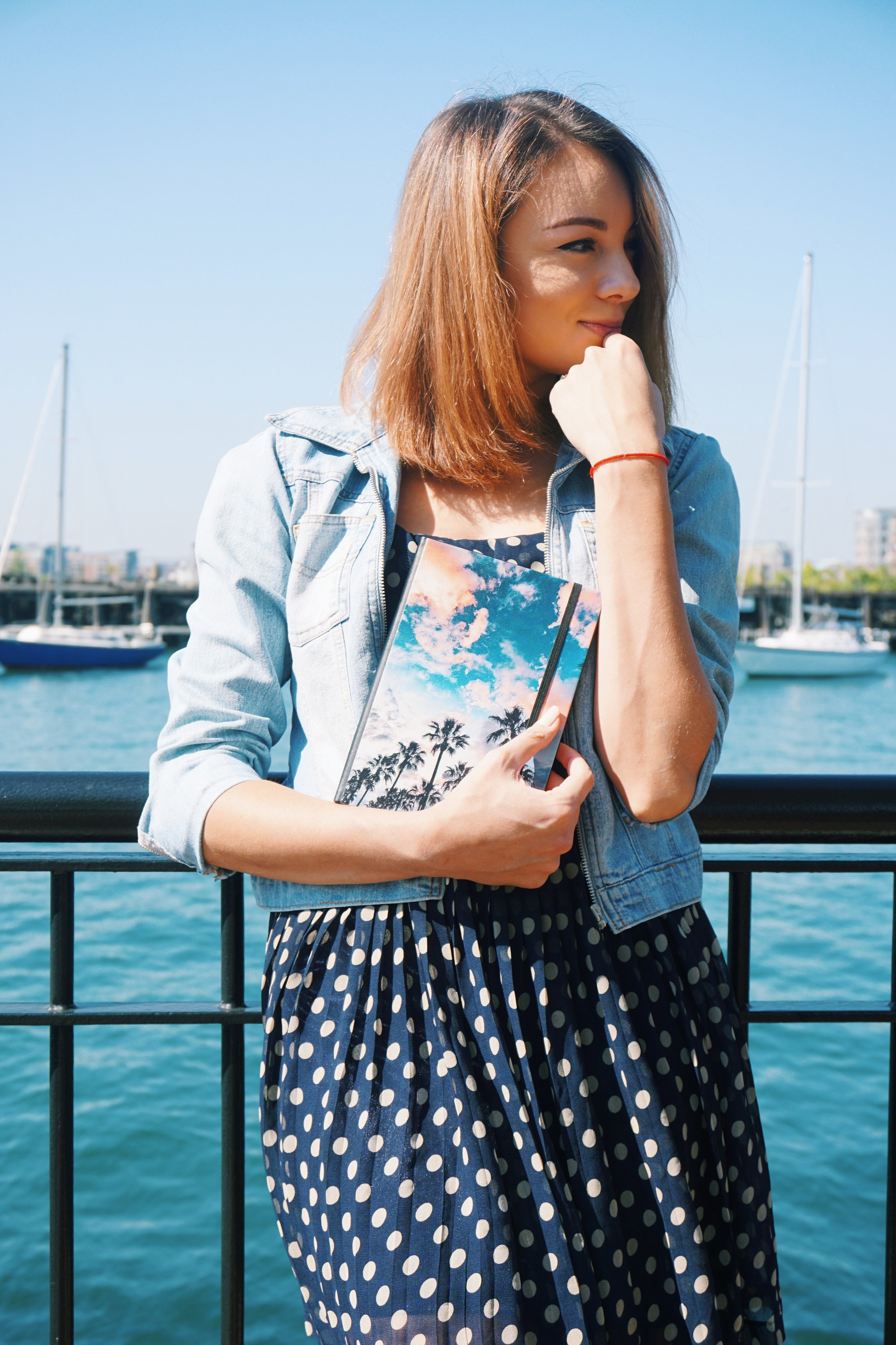 A blogger standing near the Boston pier, holding a customized design notebook, wearing a polka dot dress and a denim jacket.