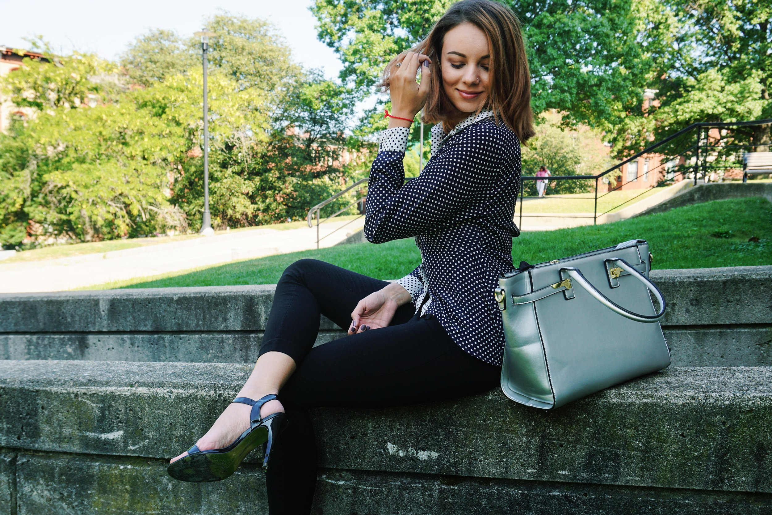 A blogger sitting in the park, wearing a polka dot blouse, black capris, black high heel sandals, and a silver purse.