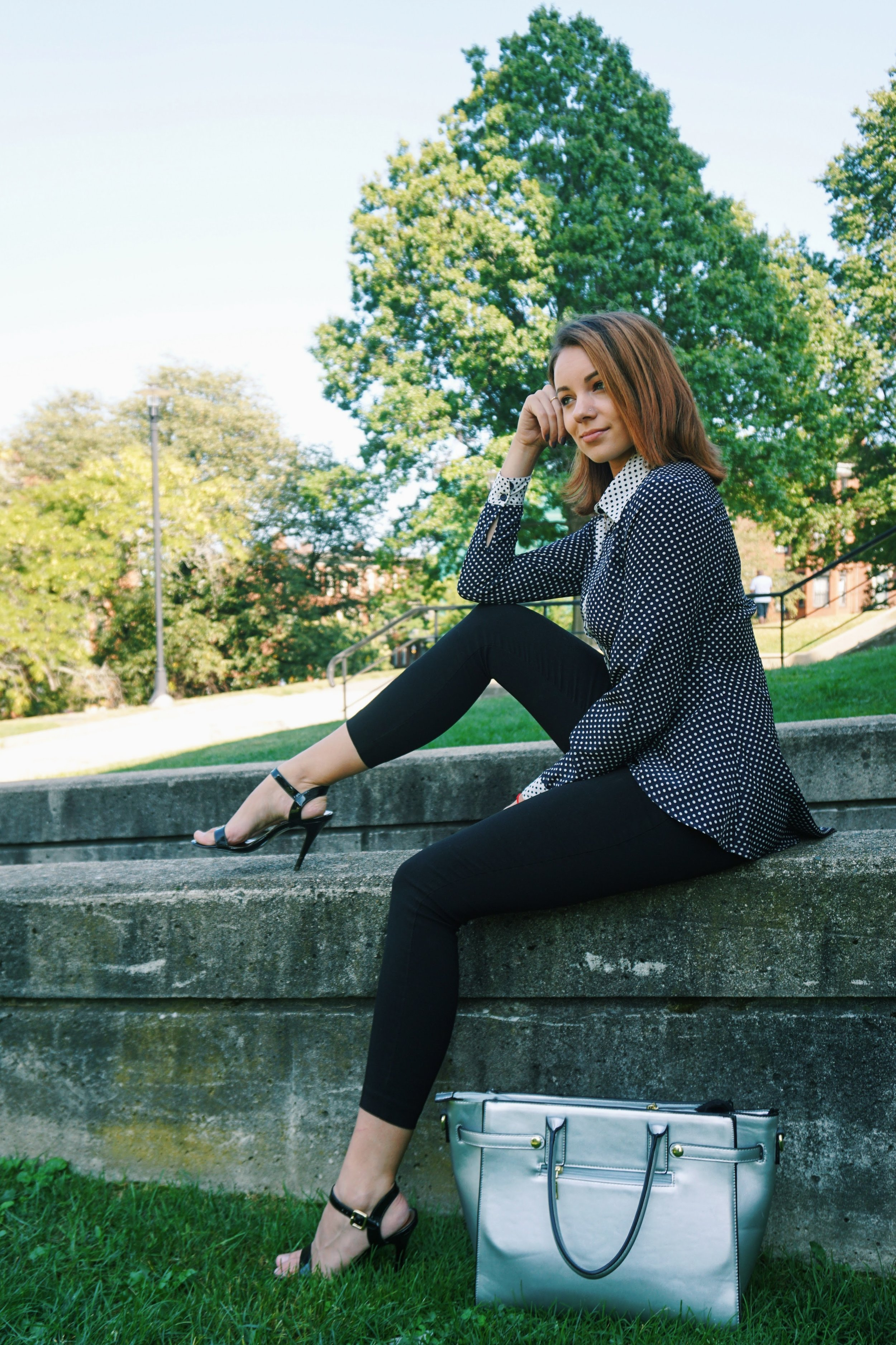 A blogger in the Boston park, wearing a black and white polka dot blouse, black capris, anf black high heeled sandals.