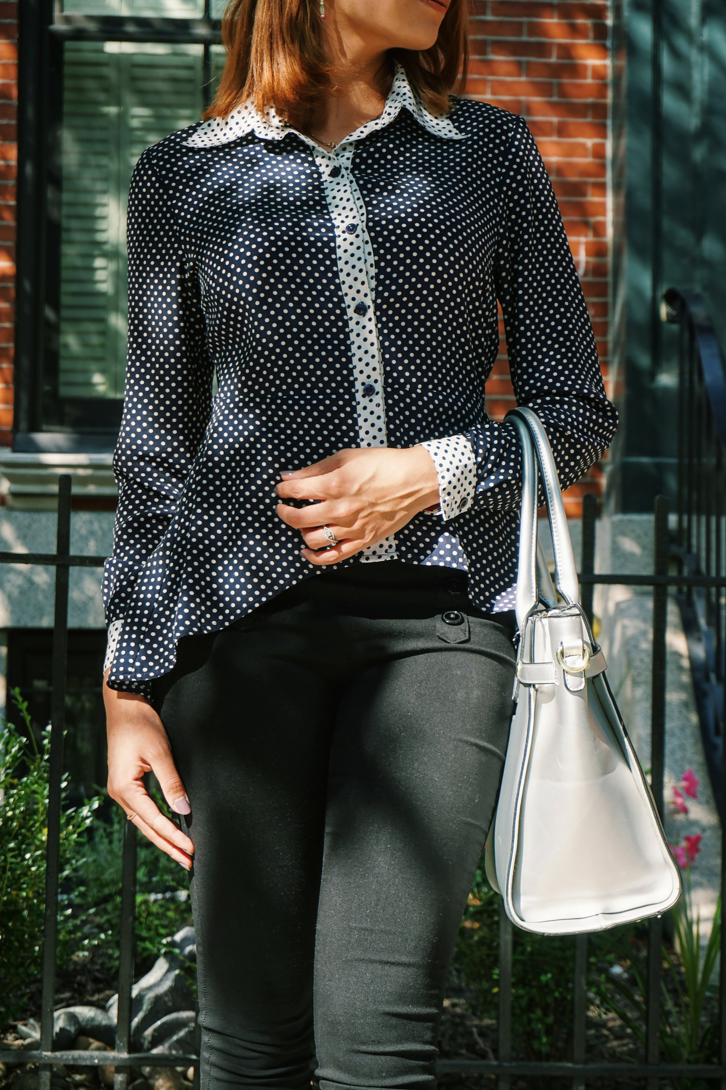 A close-up of a business casual outfit: polka dot blouse, black pants, silver bag.