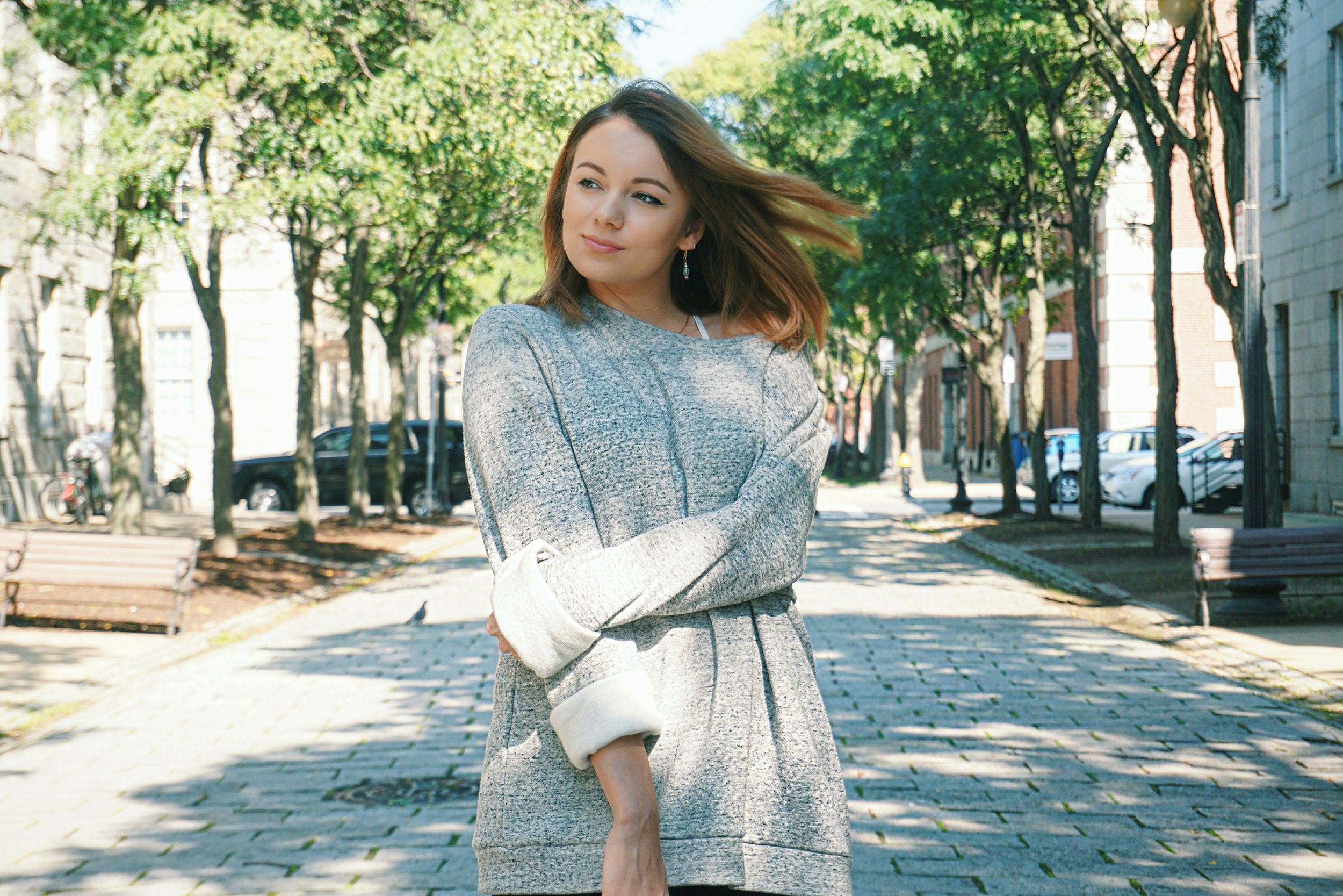 A girl wearing a gray oversized sweater.