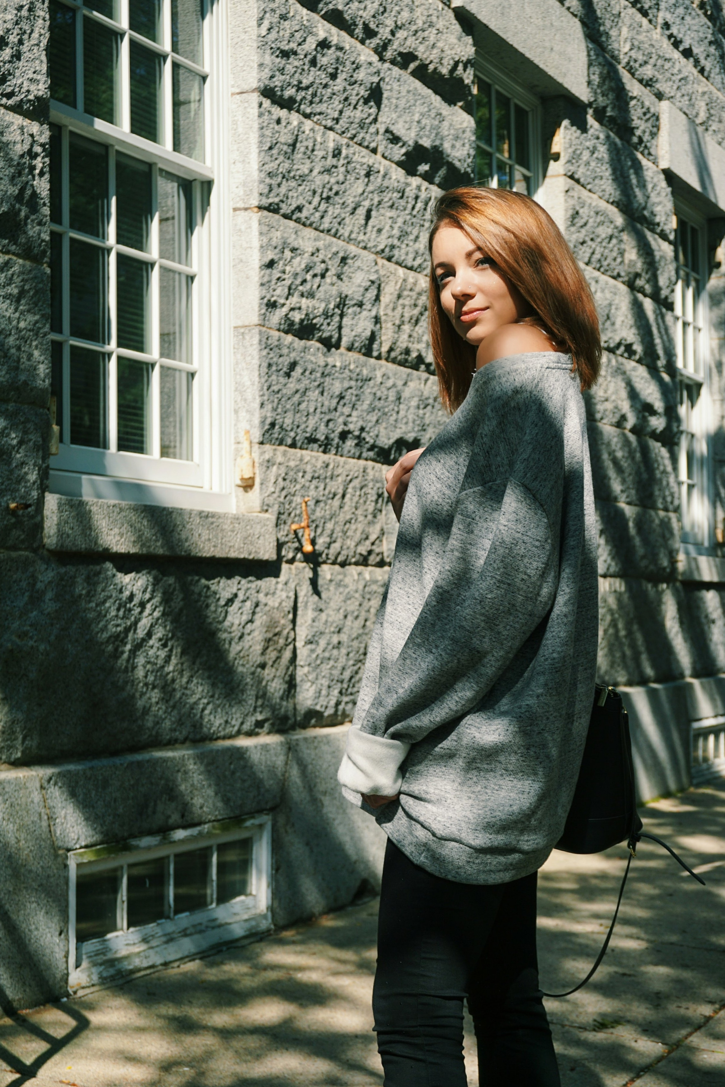 A fashion blogger standing in front of a gray building, wearing a big and long sweater, and black jeans.