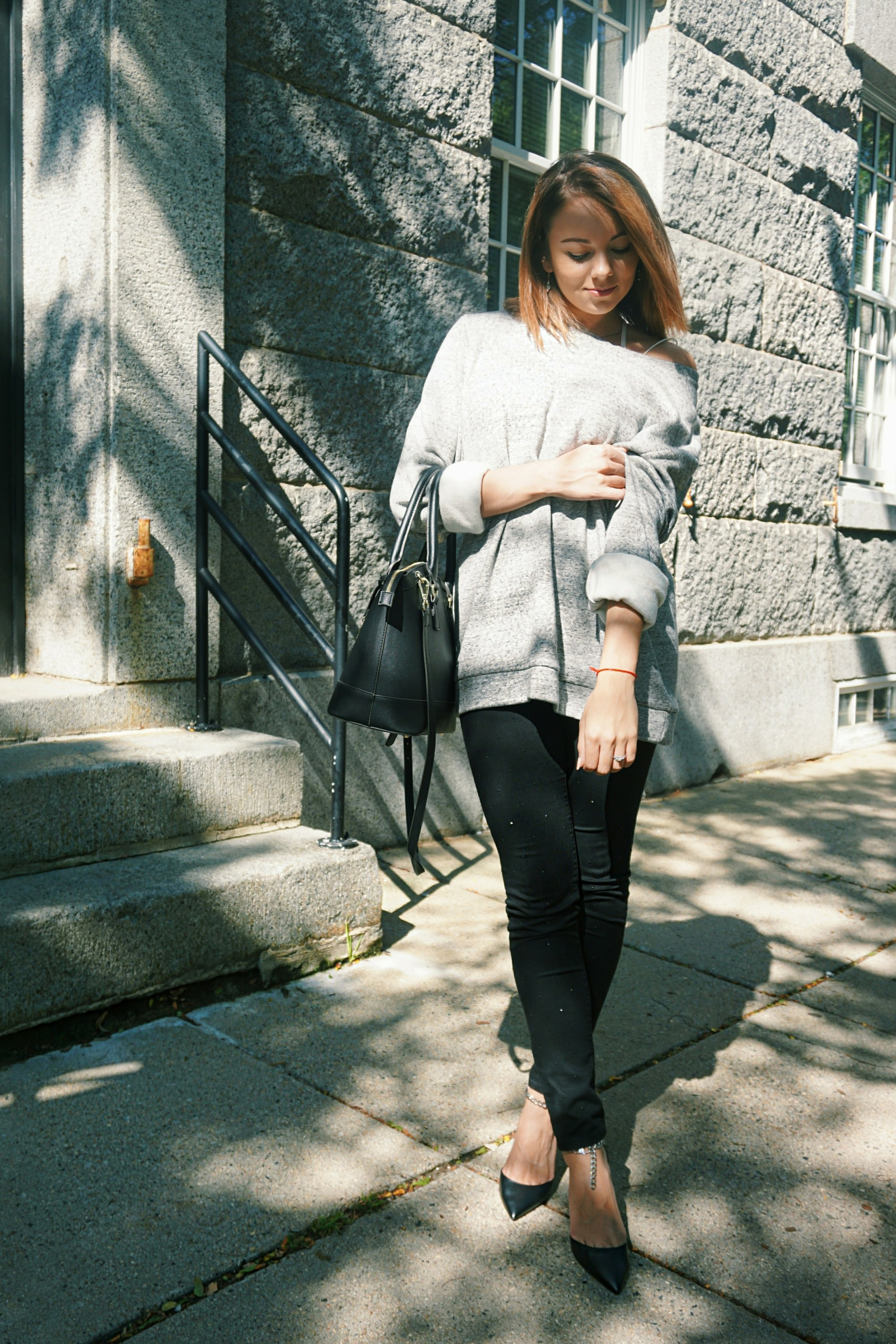 A lifestyle blogger posing in front of a gray Boston building, wearing a fall outfit.
