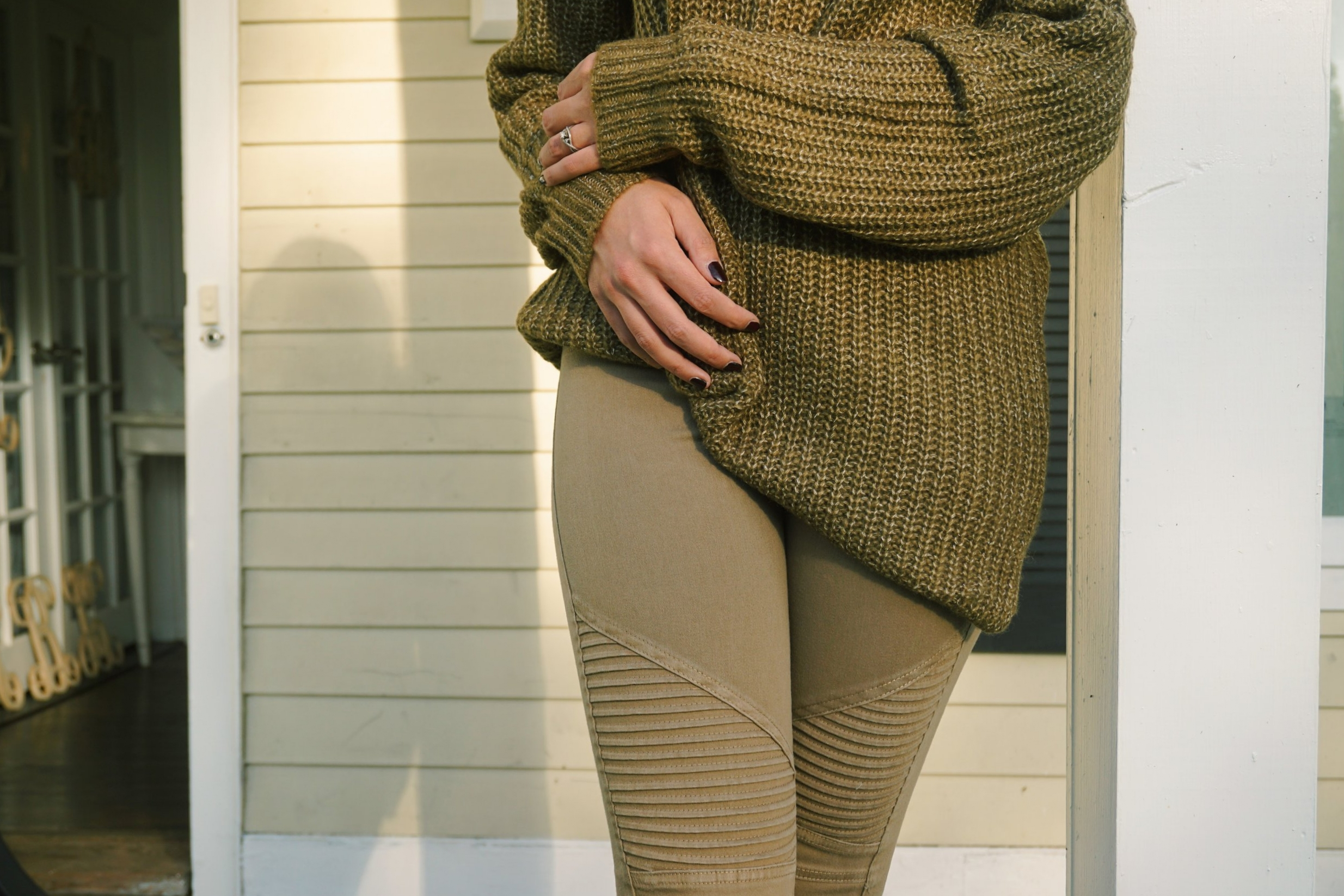 Details of a fall outfit: woven olive sweater and olive jeggings.
