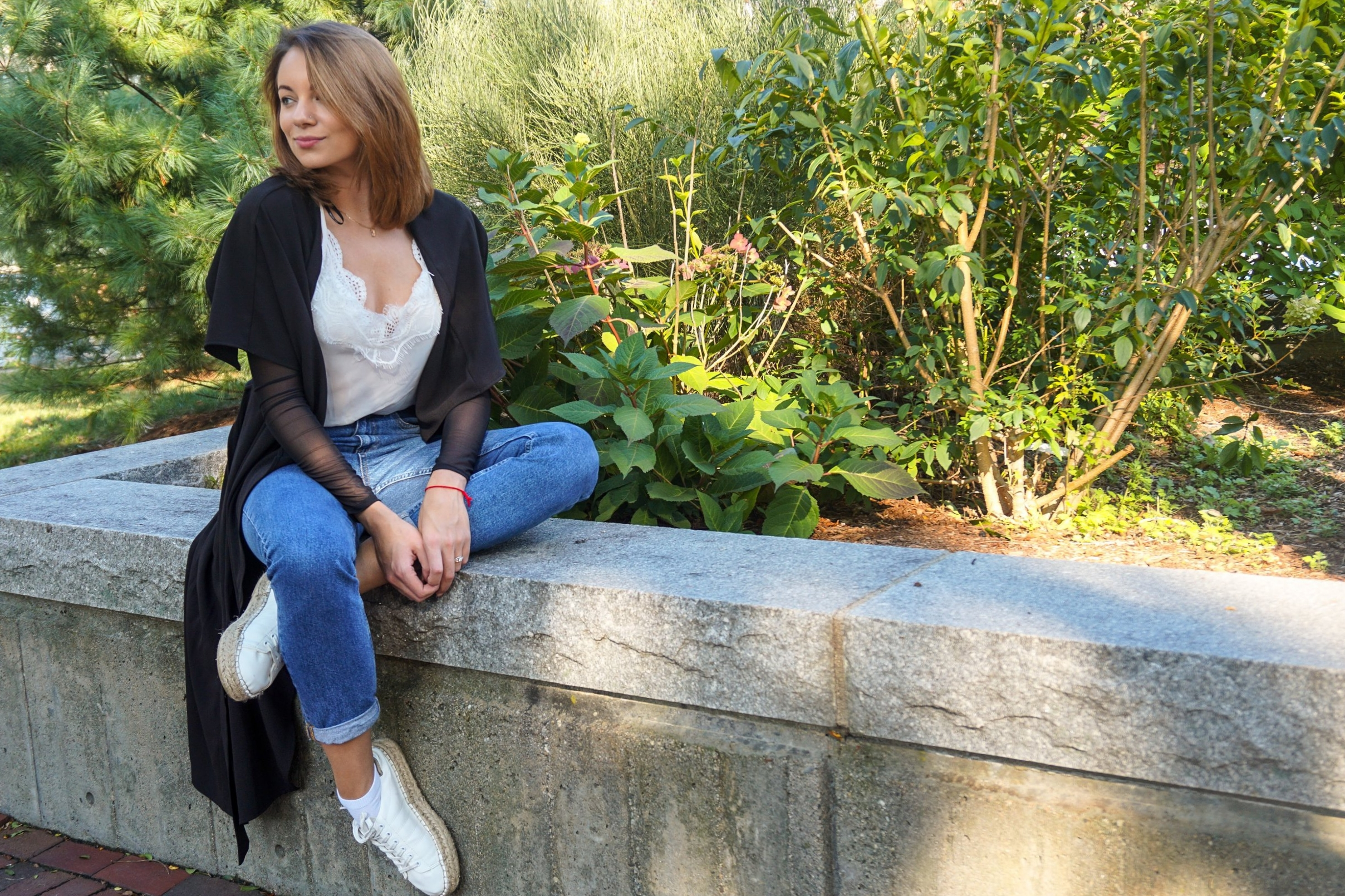 A blogger sitting in the park, wearing blue mom jeans, white tank top, black duster, and white sneakers.