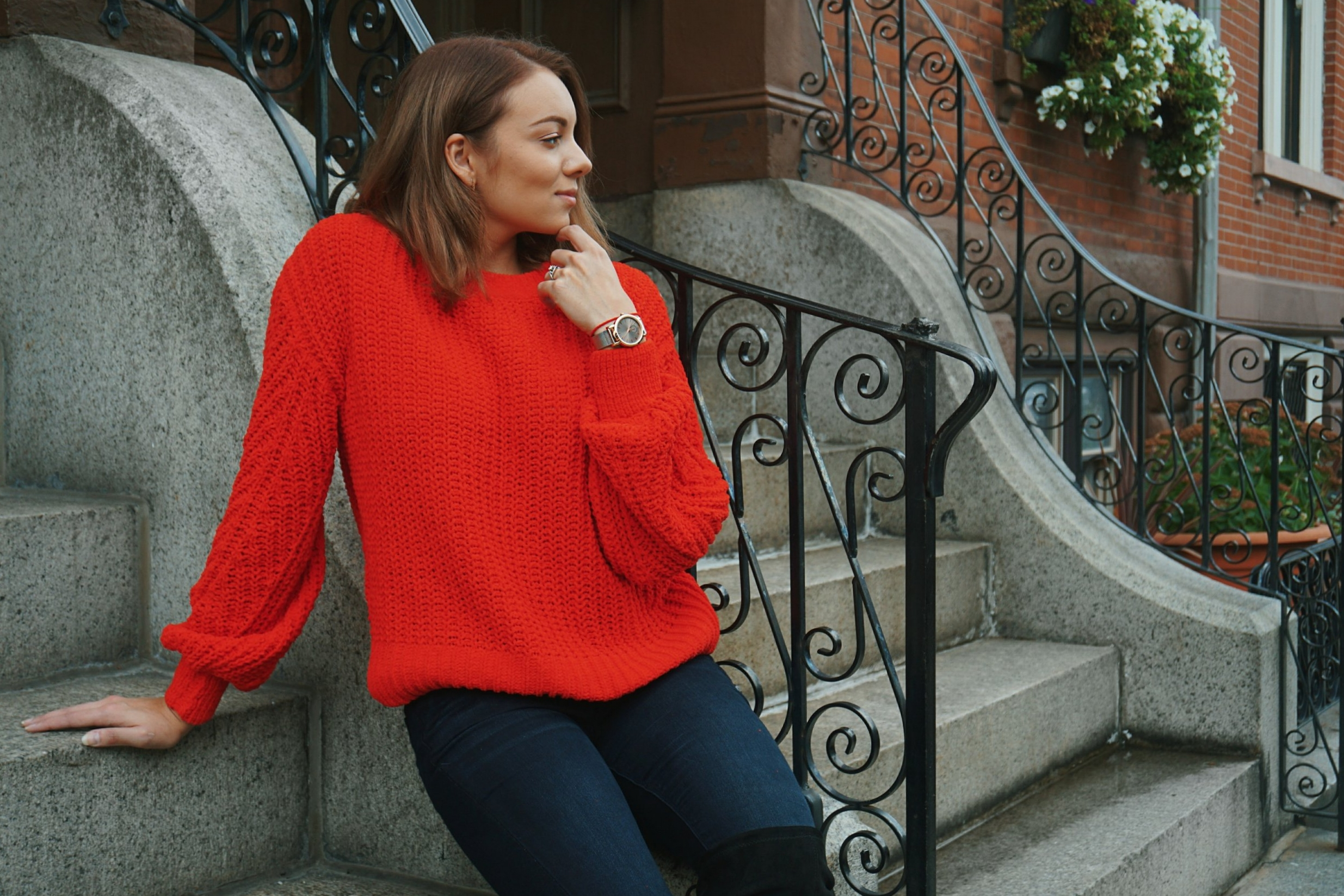 A girl sitting on stone steps, wearing a red oversized sweater and jeans.