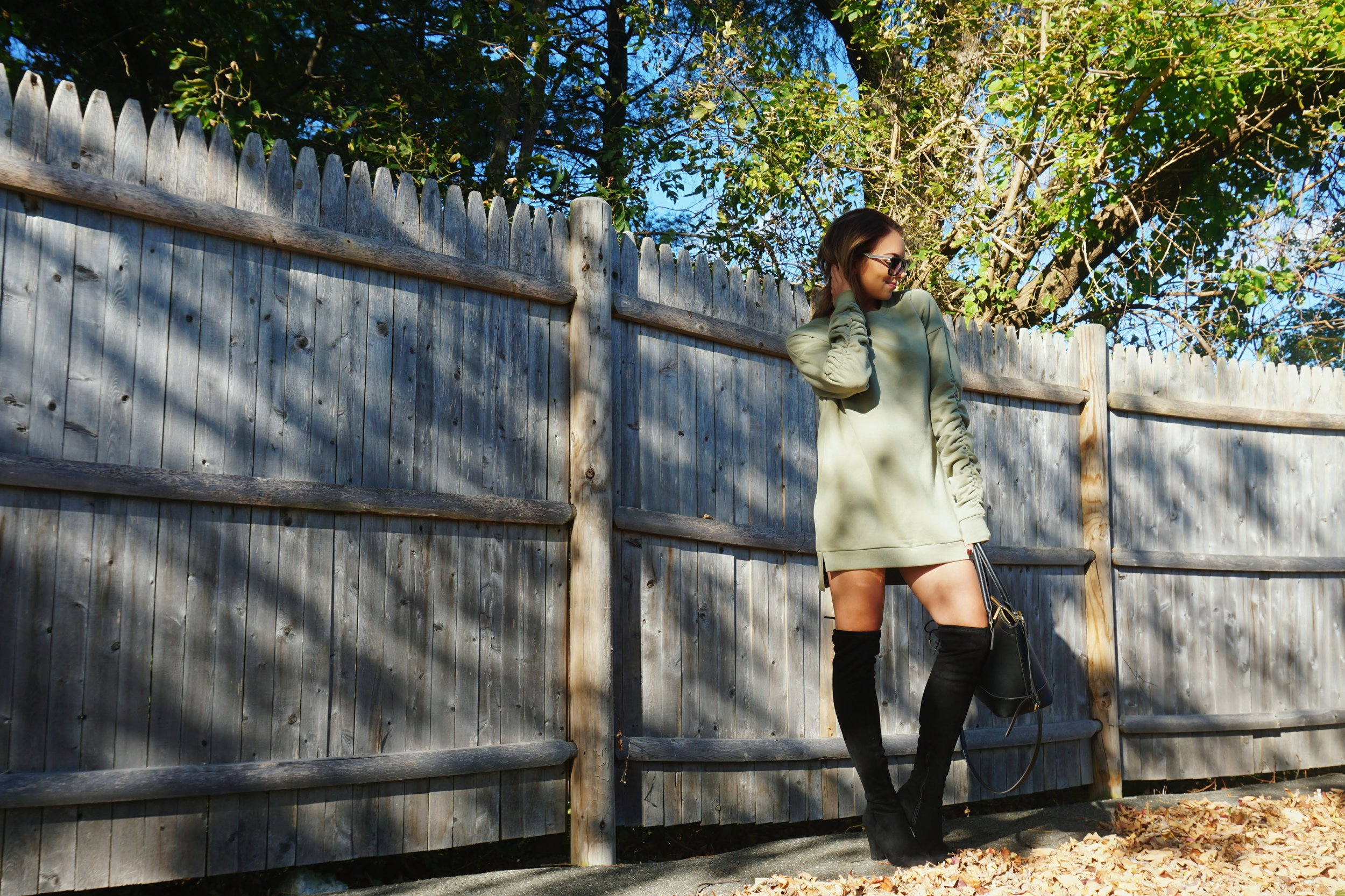 A blogger wearing a green sweater dress, black knee-high boots, and a black purse.