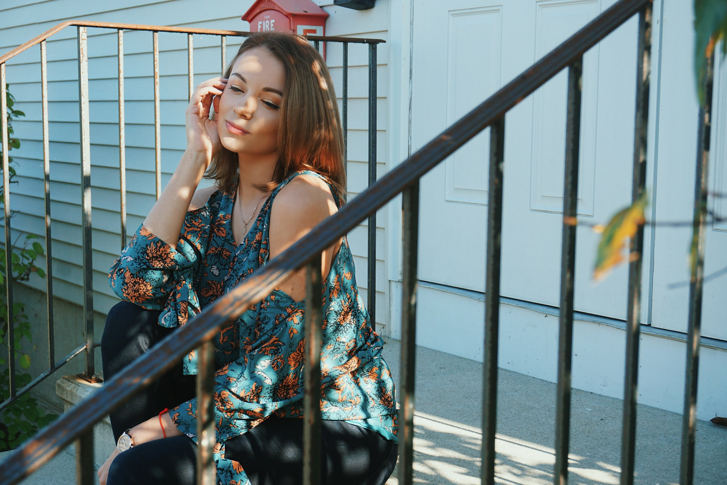Lifestyle blogger wearing a blue floral open-shoulder top.