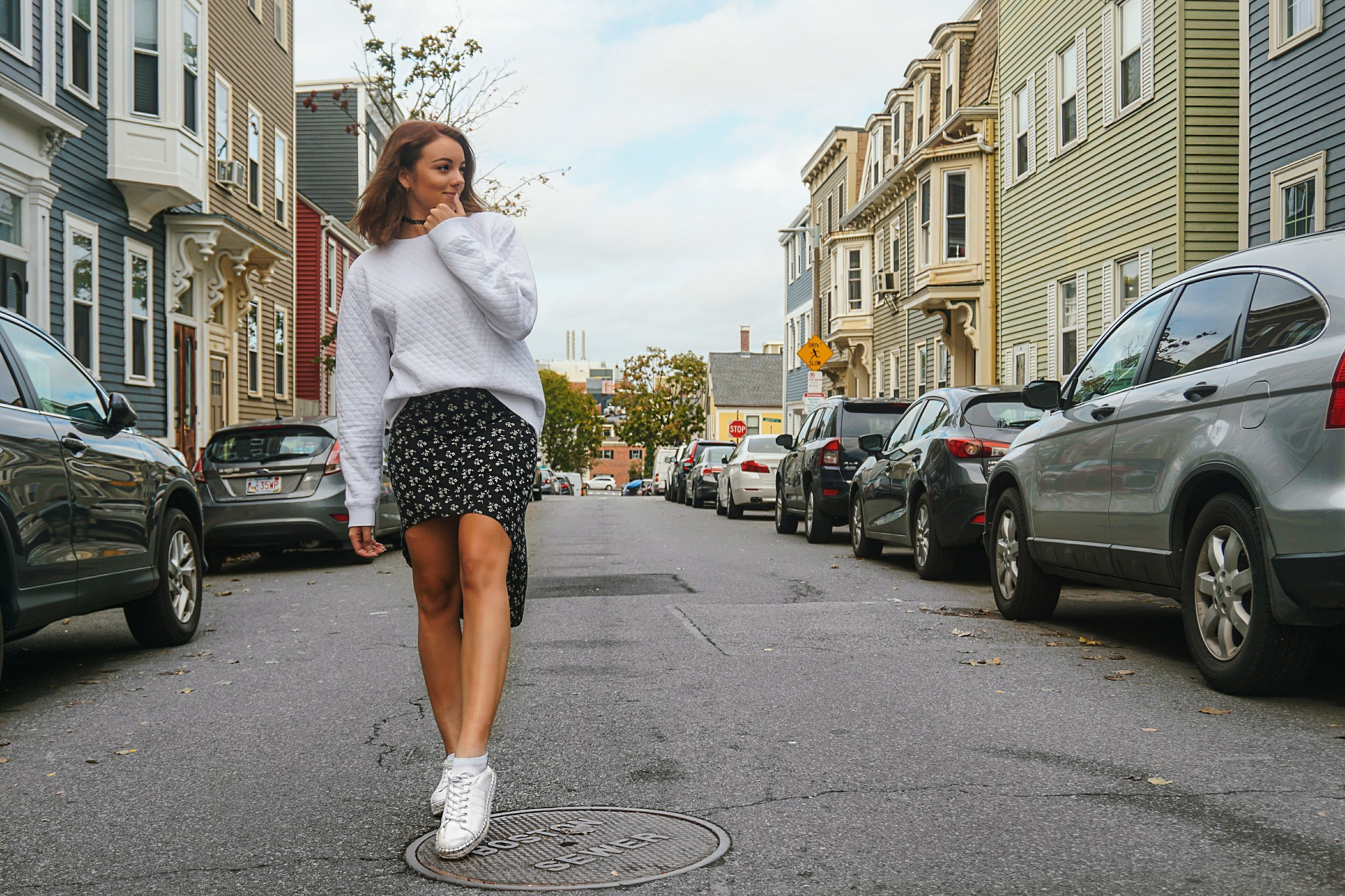 A Boston blogger wearing an oversized white sweatshirt, black skirt, and white sneakers.