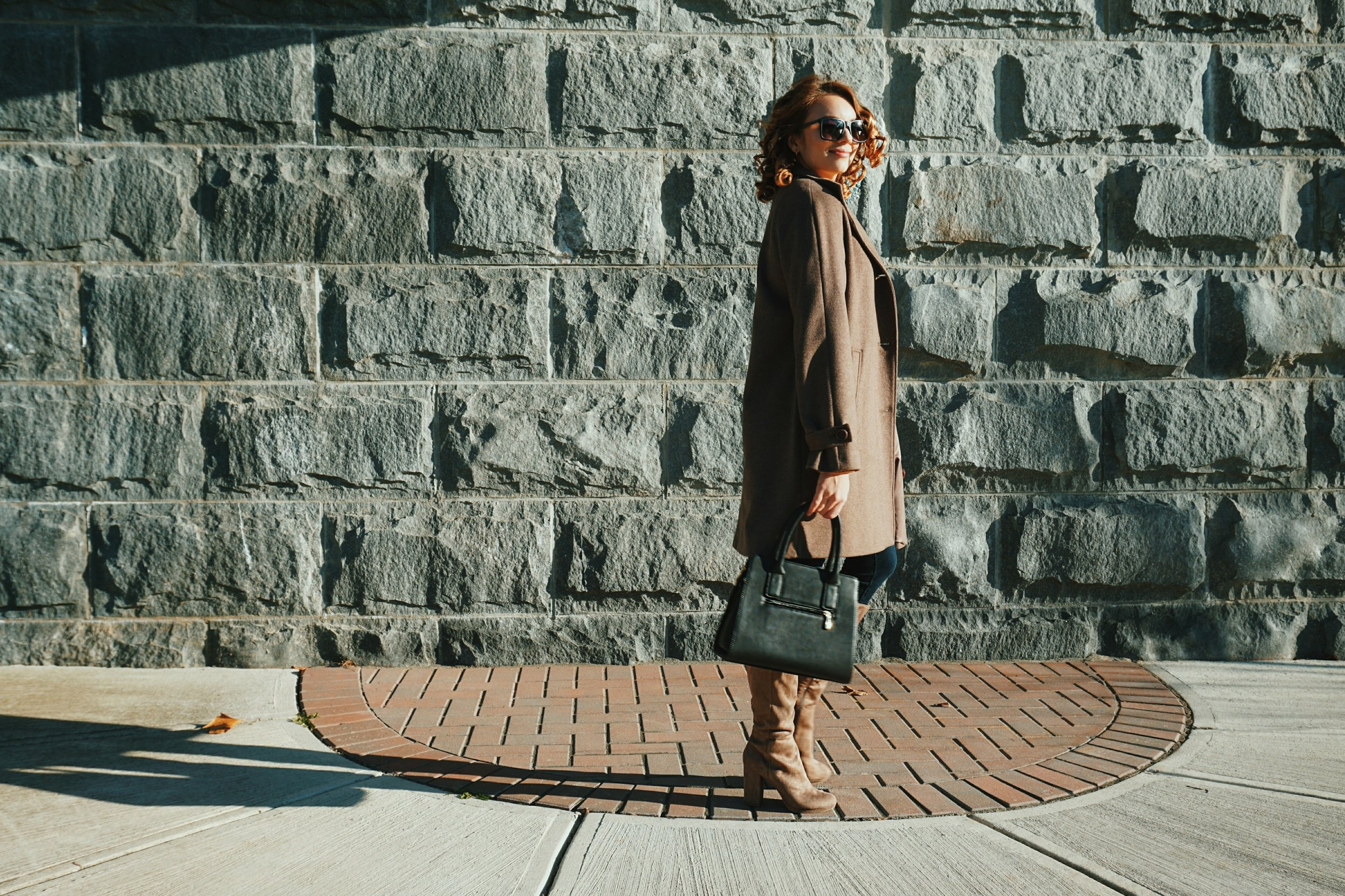 A fashion blogger standing near a stone wall, wearing a brown autumn coat, brown boots, and a black bag.