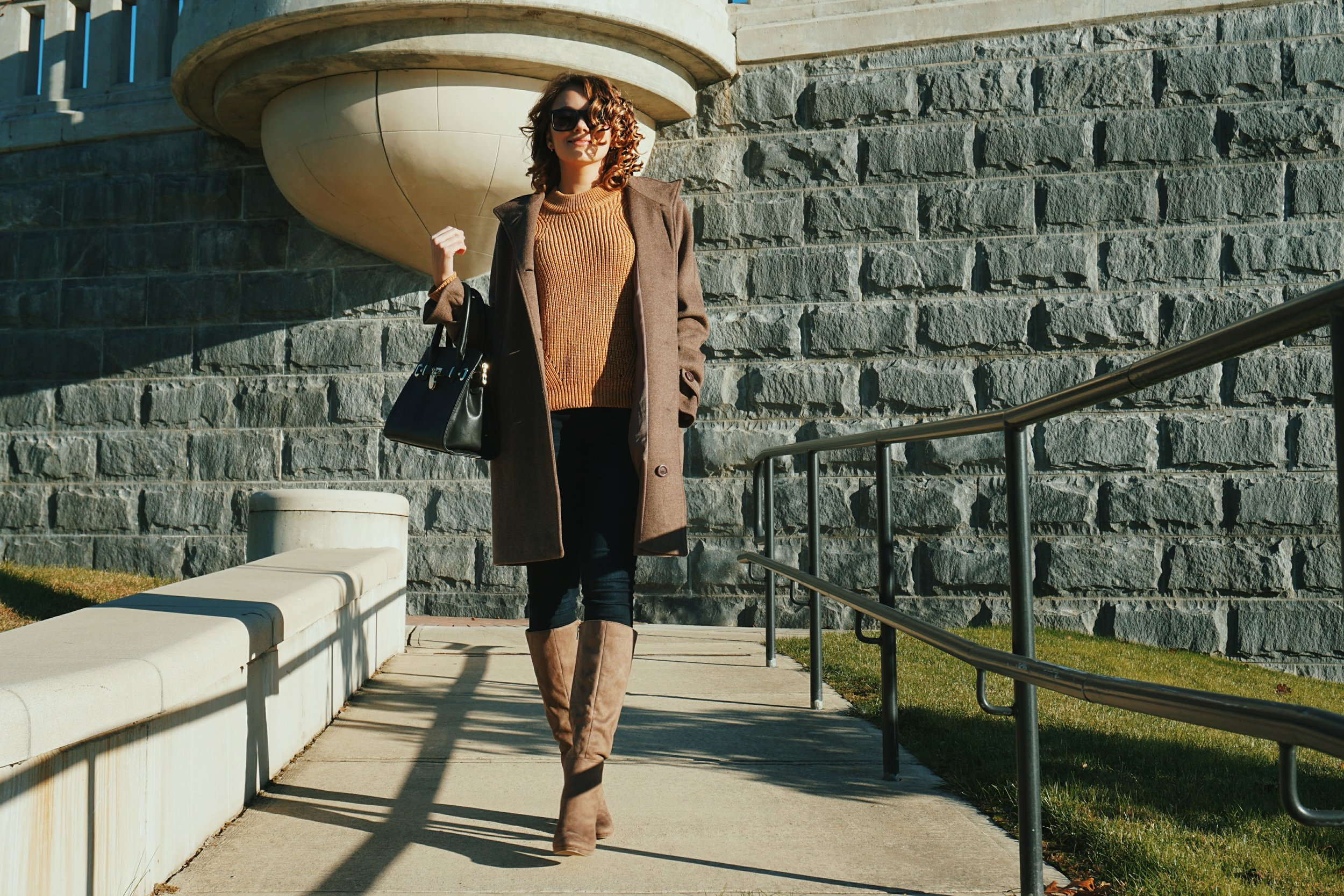 A fashion blogger walking away from a stoned wall, wearing high heeled brown boots, brown baggy coat, light brown sweater, and a black bag.