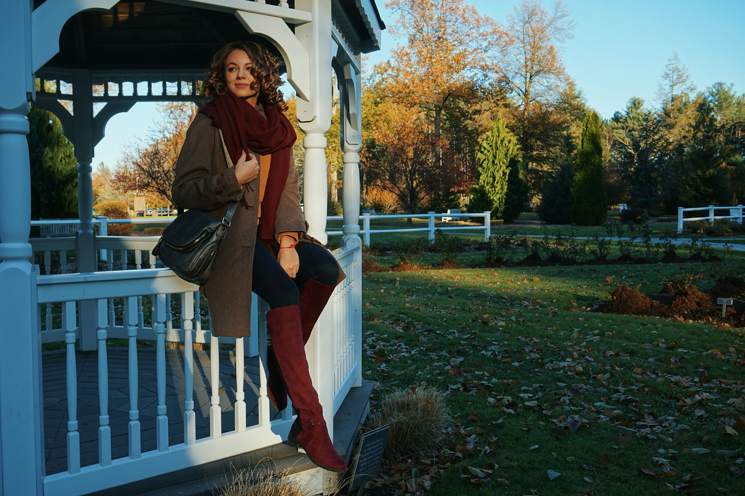 A blogger sittin on the side of the gazebo, wearing a brown coat, maroon boots, maroon scarf, and a gray purse.