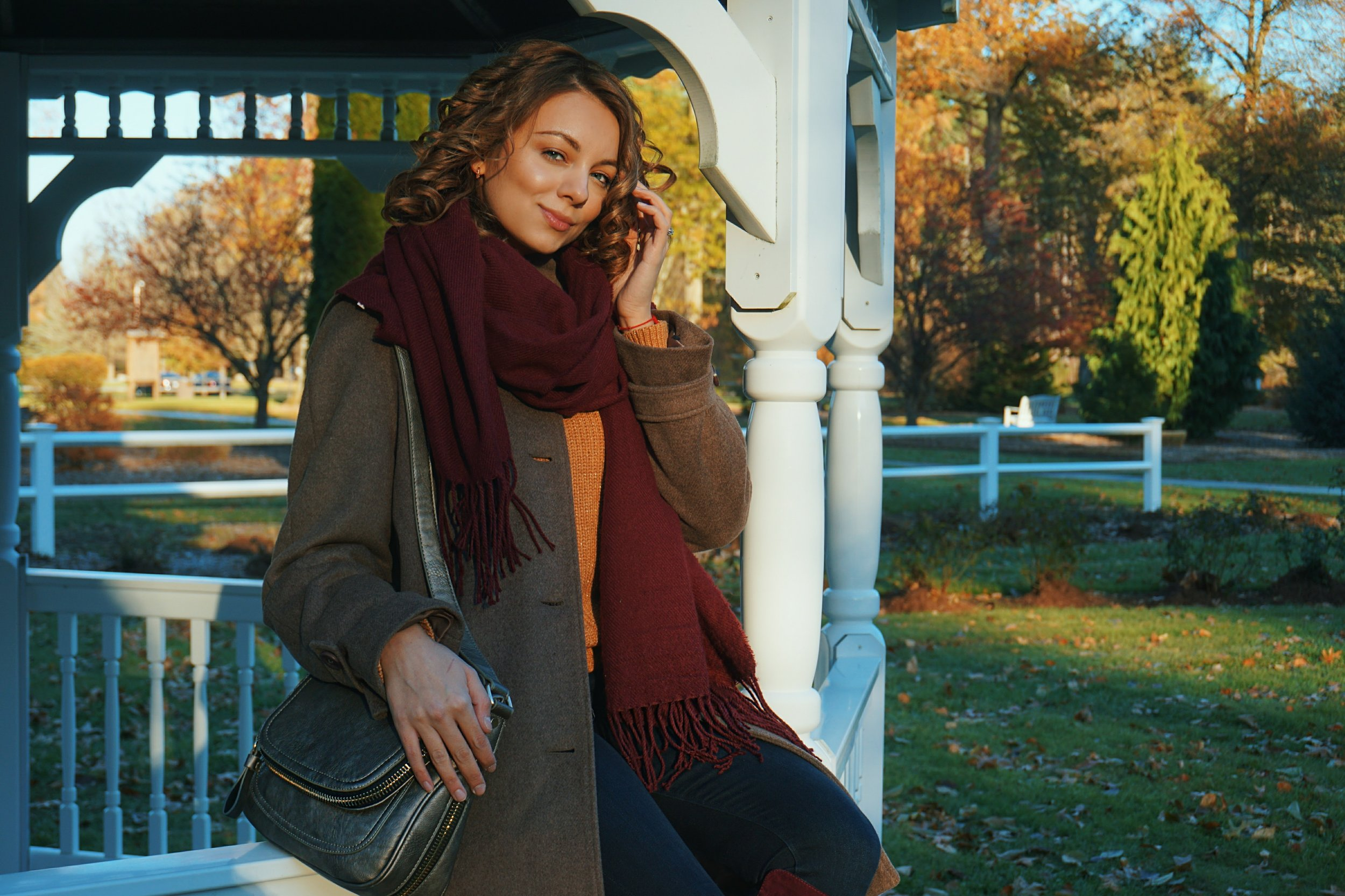A blogger posing by the gazebo, wearing a warm autumn look.