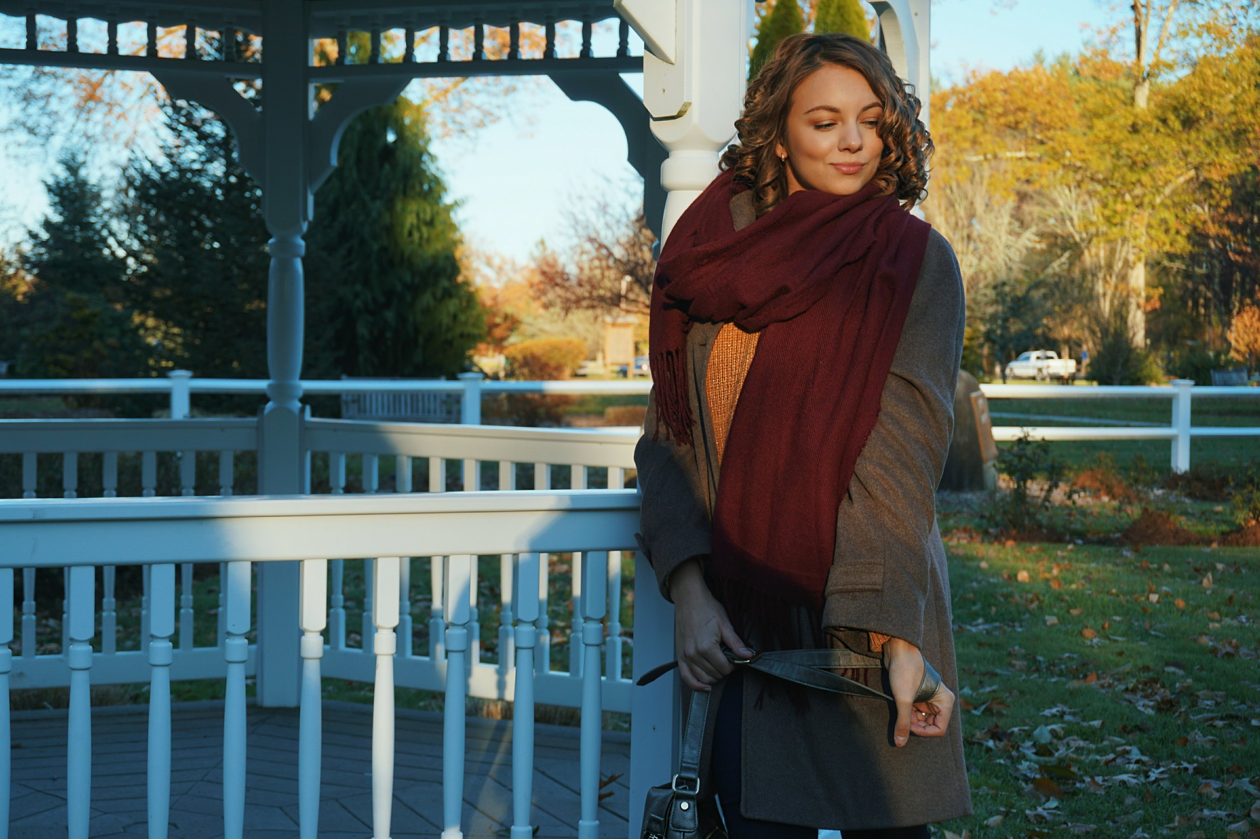 A beauty blogger wearing a fall look: brown coat and sweater, maroon scarf, and gray purse.