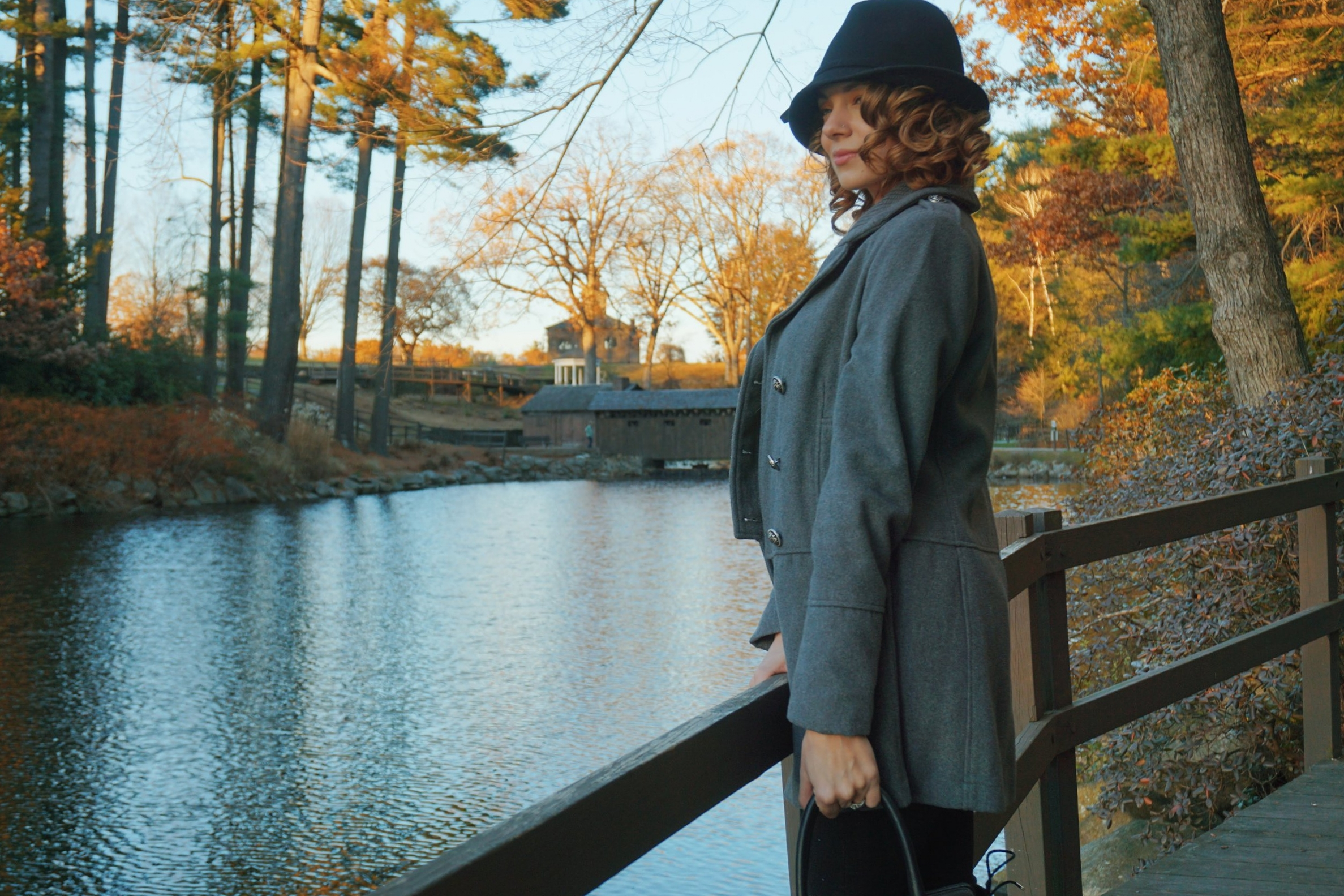 A beauty blogger with curly hair wearing a fall look : black hat, gray coat, black jeans, boots, and bag.