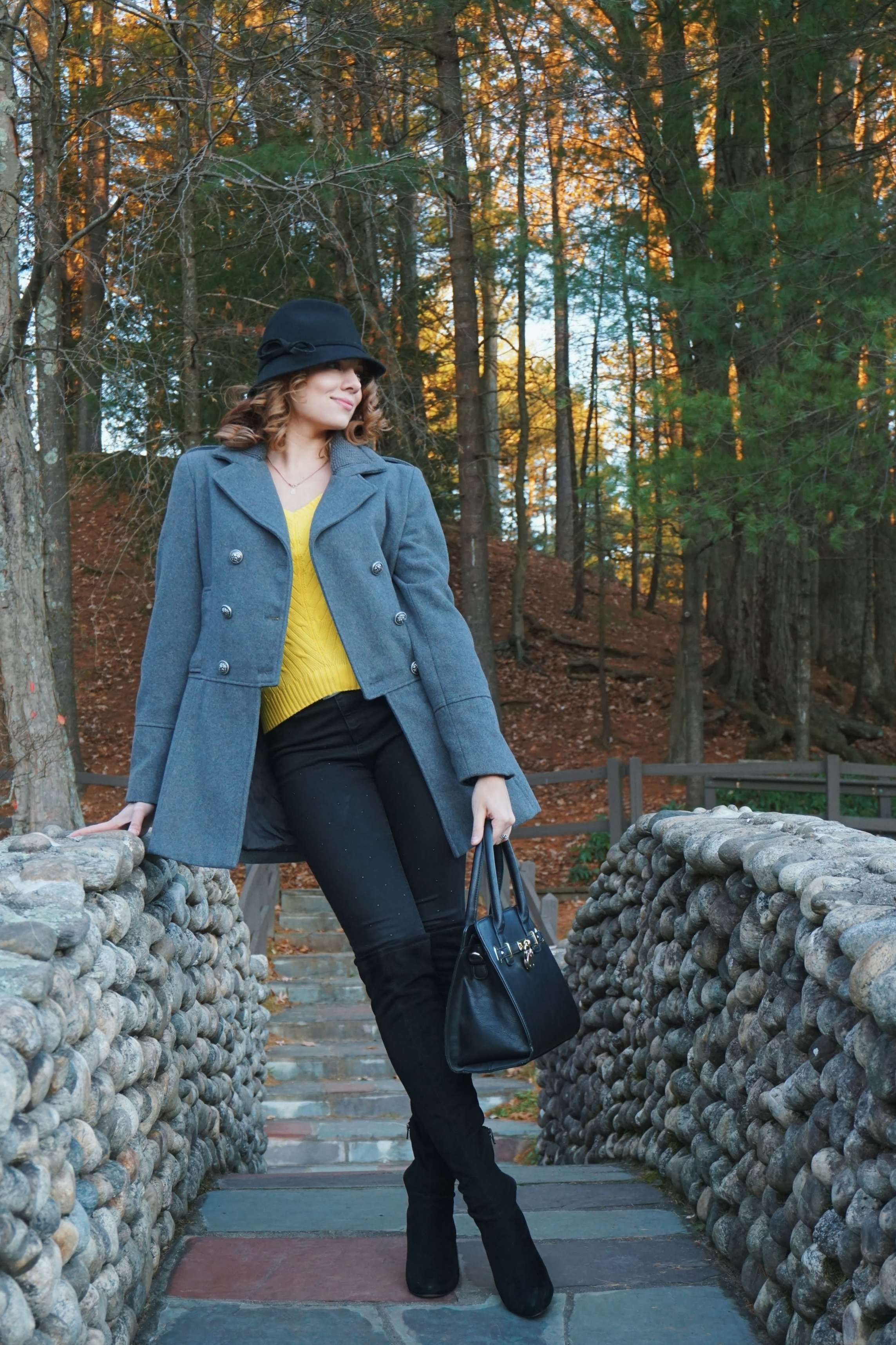 Fall outfit inspiration 2017: black Jennifer Lopez jeans, yellow knitted sweater, thigh high boots, gray woolen sweater, black hat, and a black bag.