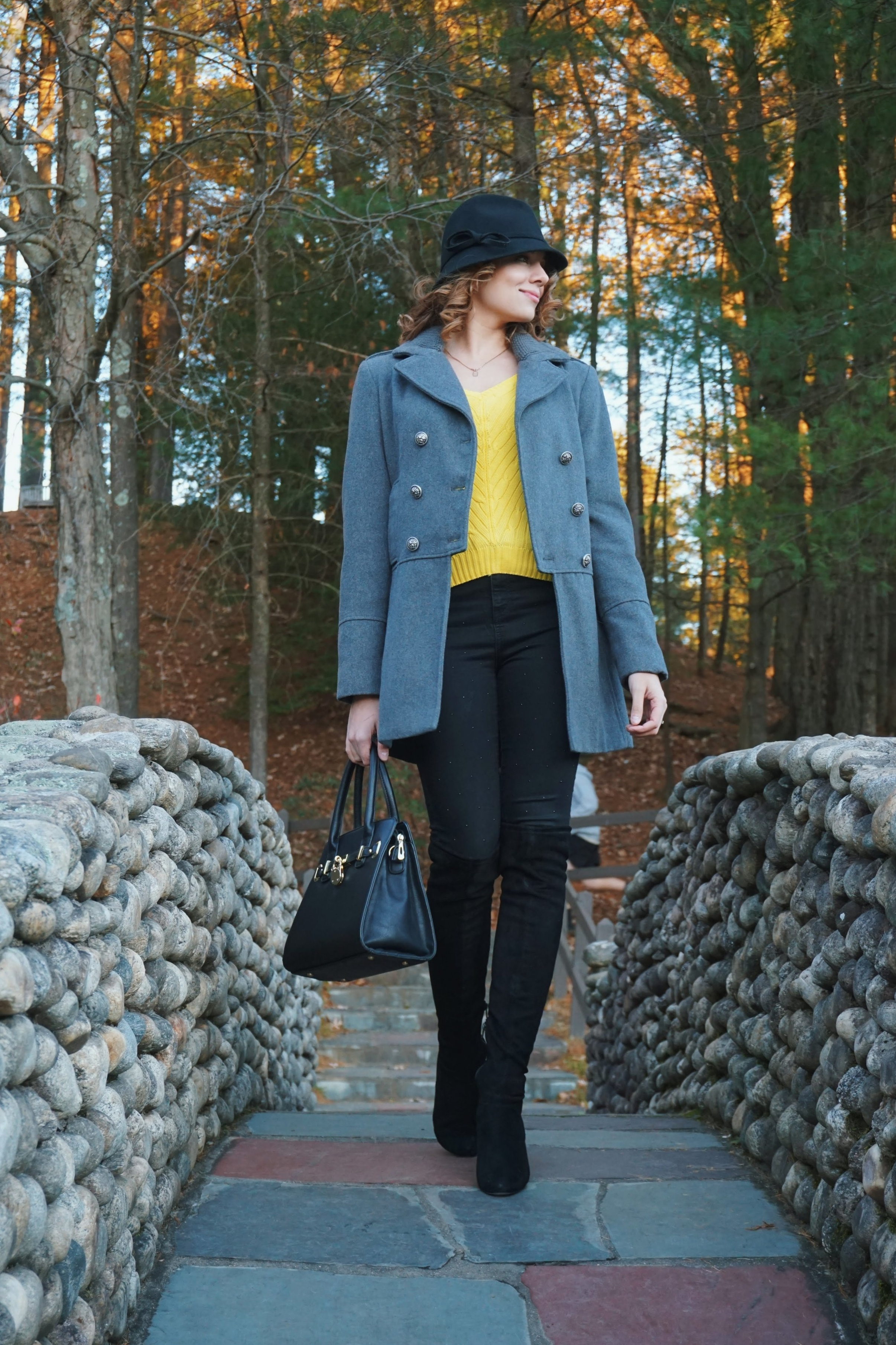 An example of a fall outfit: gray coat, yellow sweater, black jeans and boots and hat.