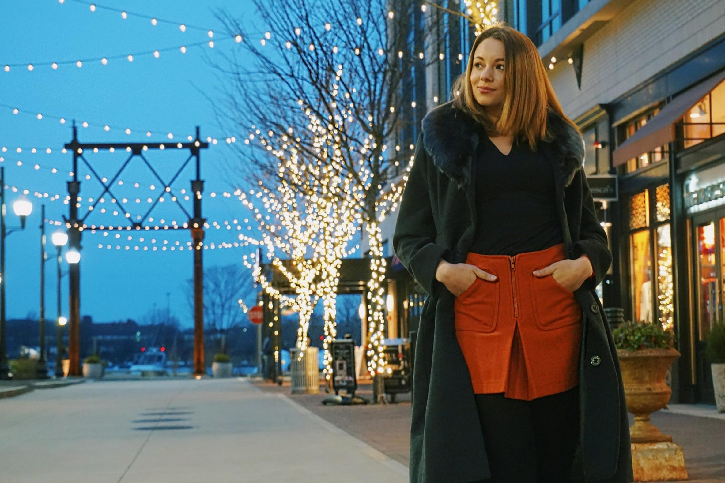 A blogger standing near Christmas lights, wearing a gray coat, orange skirt, black top.
