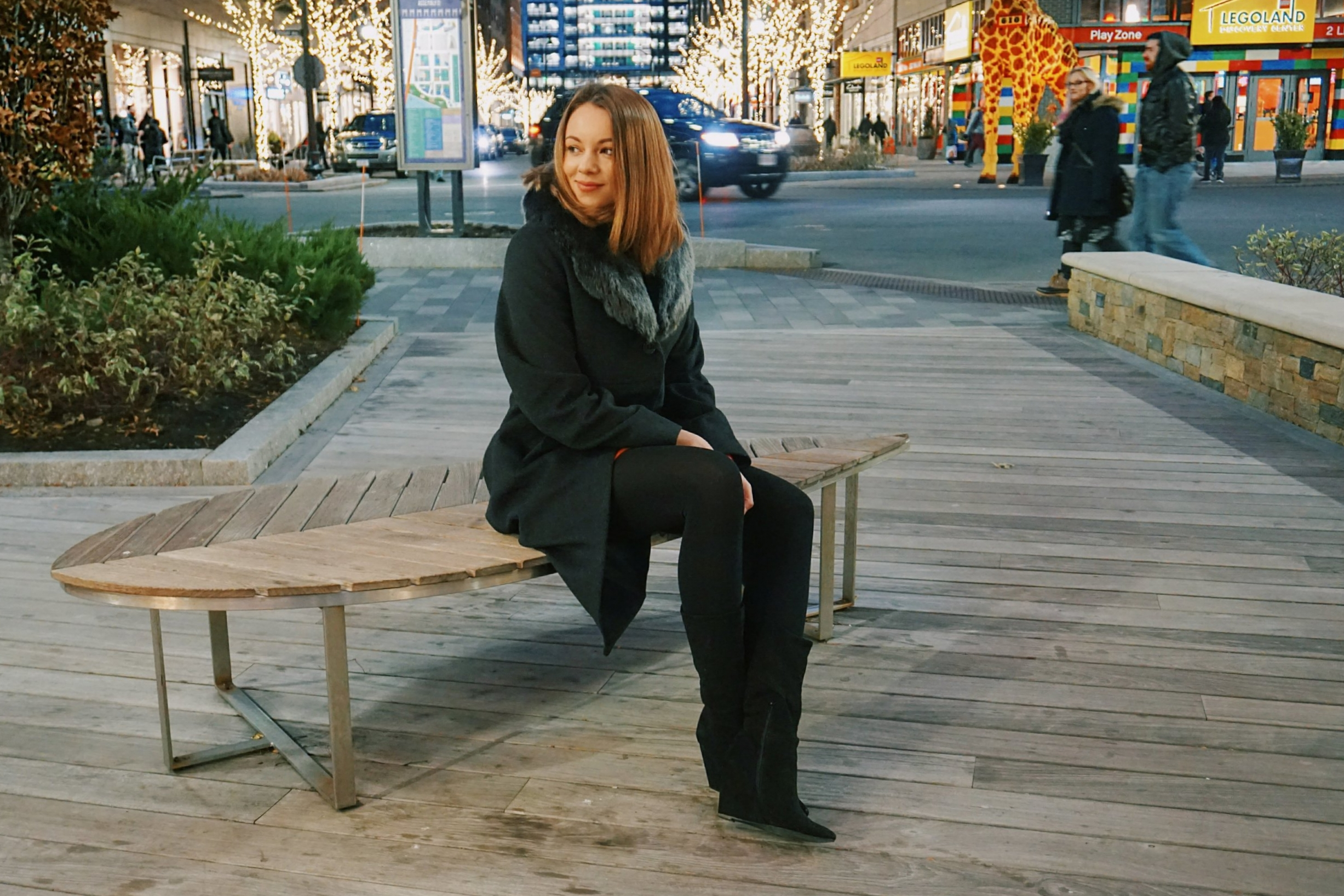 A beauty blogger sitting on the bench surrounded by Christmas lights and small shops.