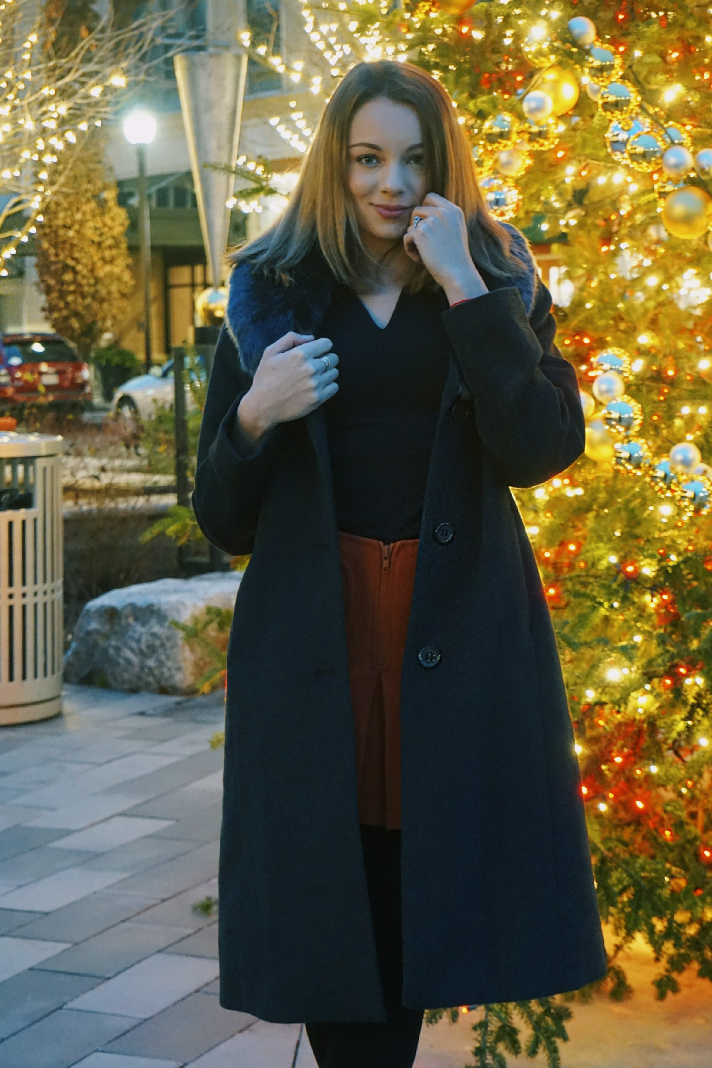 A blogger standing in front of a Christmas tree.