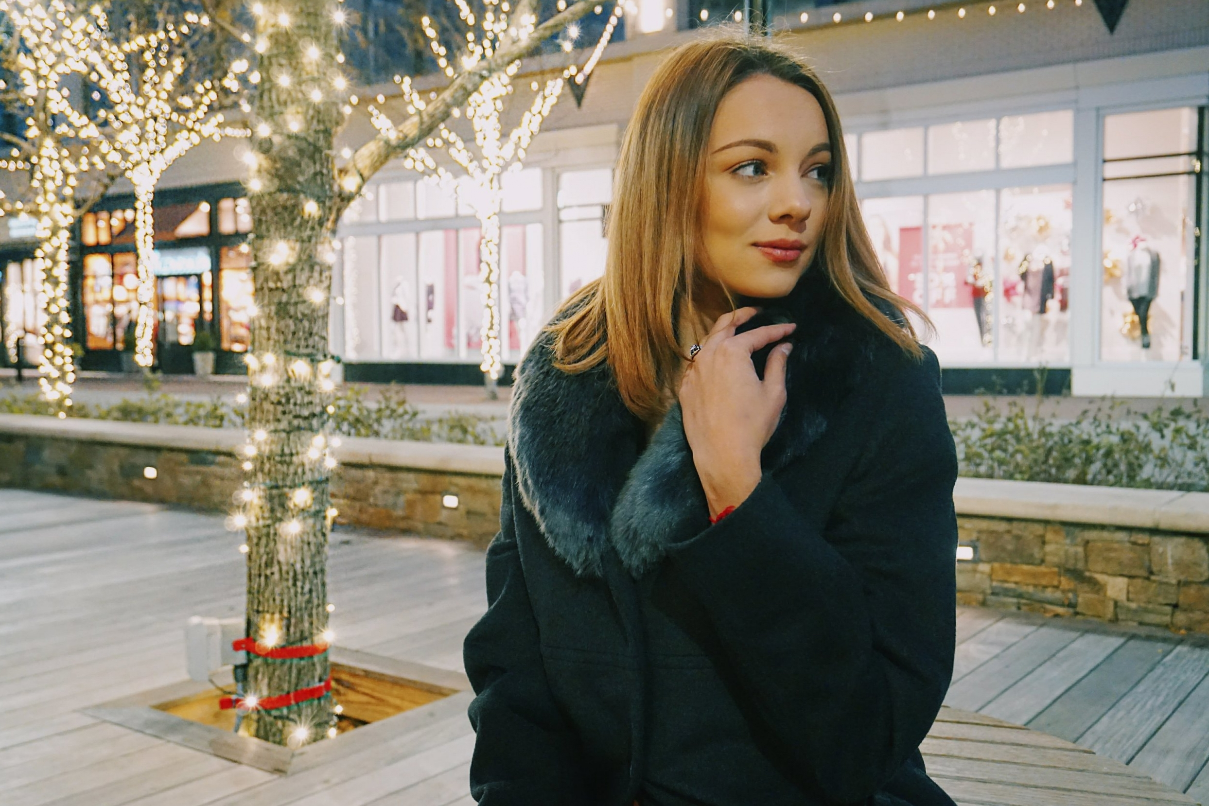 A blogger sitting on the bench outside, and Christmas lights are wrapped around the trees behind her.