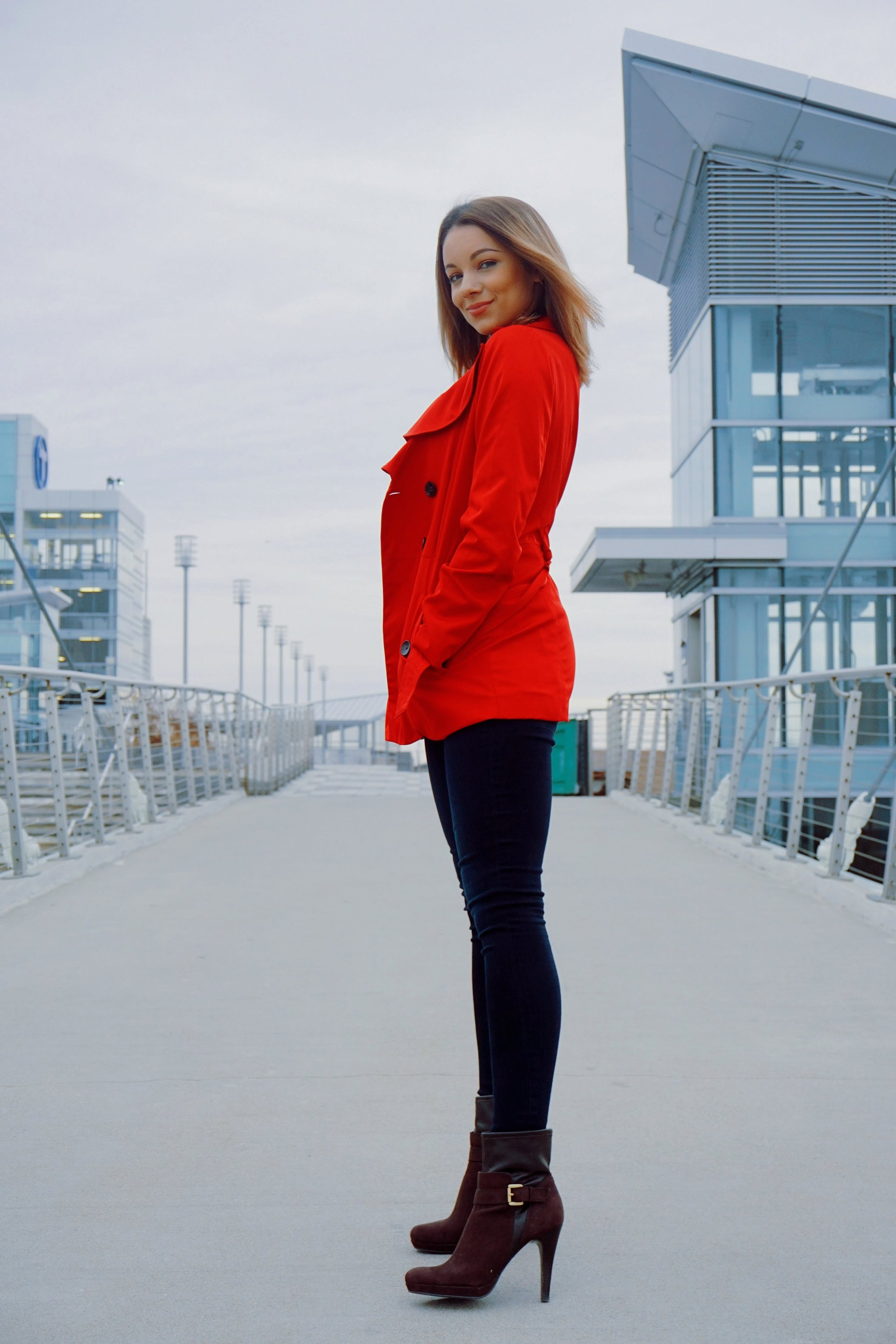 A blogger wearing a red coat, dark blue jeans, and brown booties.