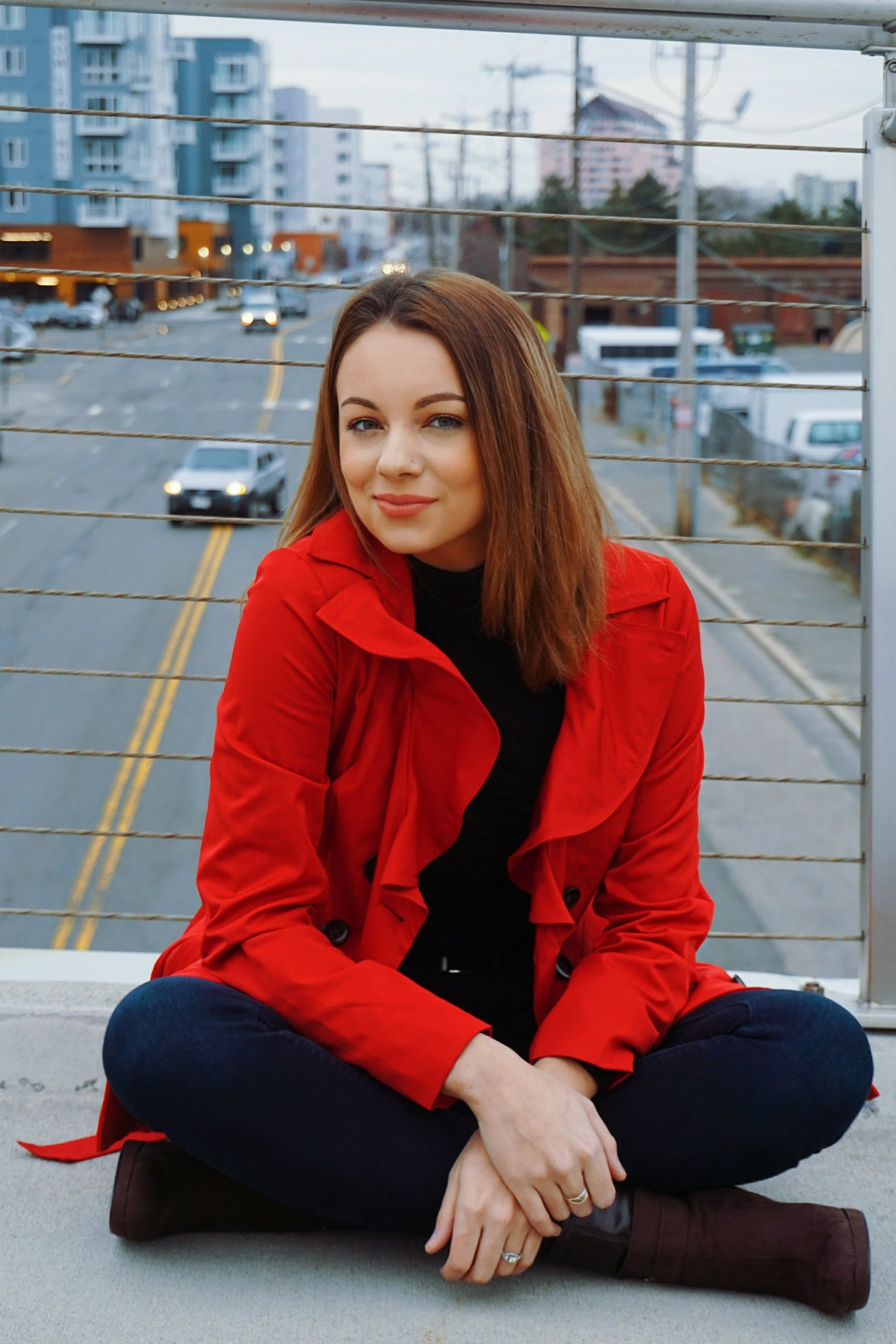 Blogger sitting on the bridge with cars driving in the background, wearing a spring outfit with red coat.