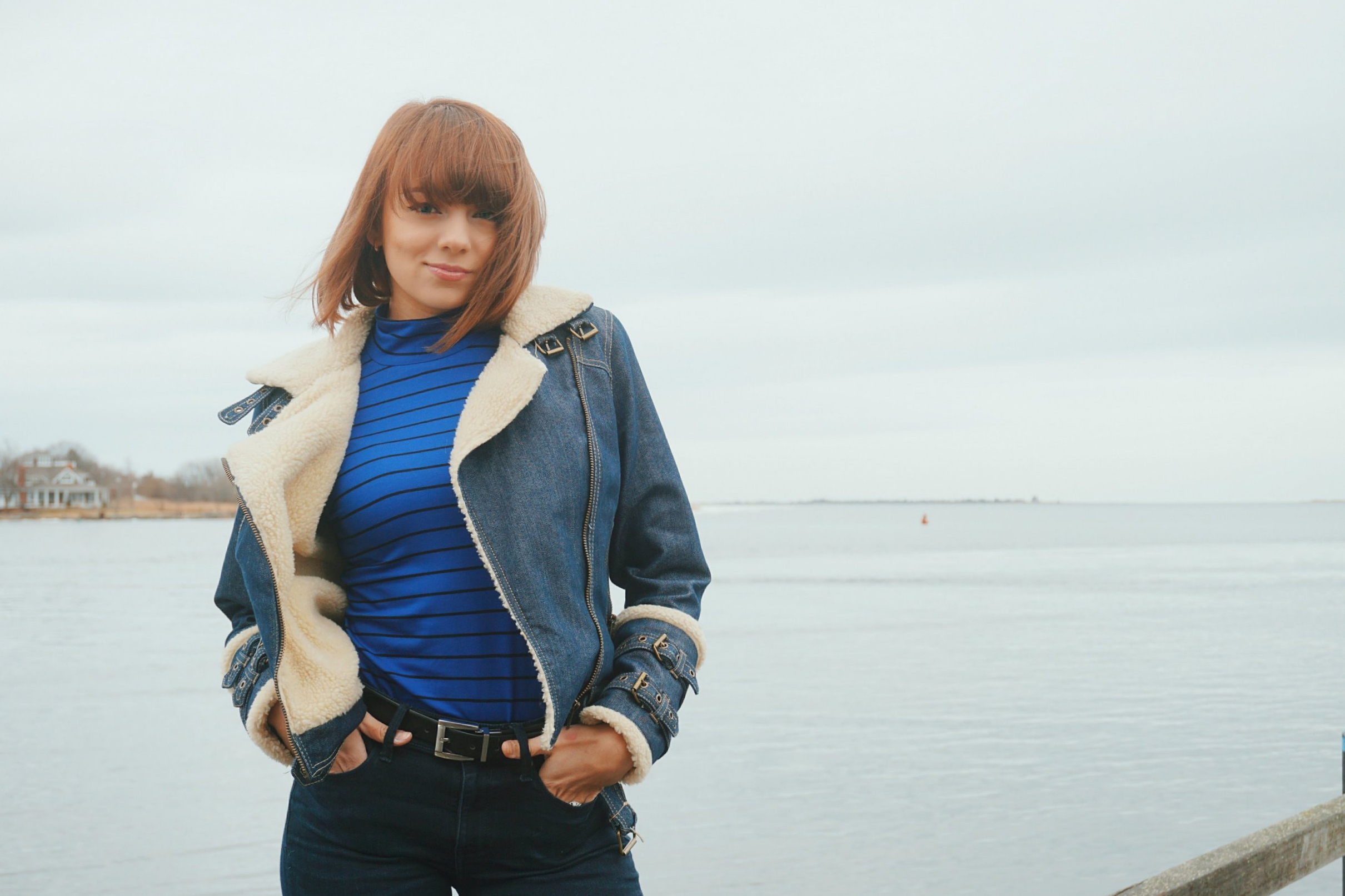 A girl wearing a blue turtleneck, denim winter jacket, and jeans.