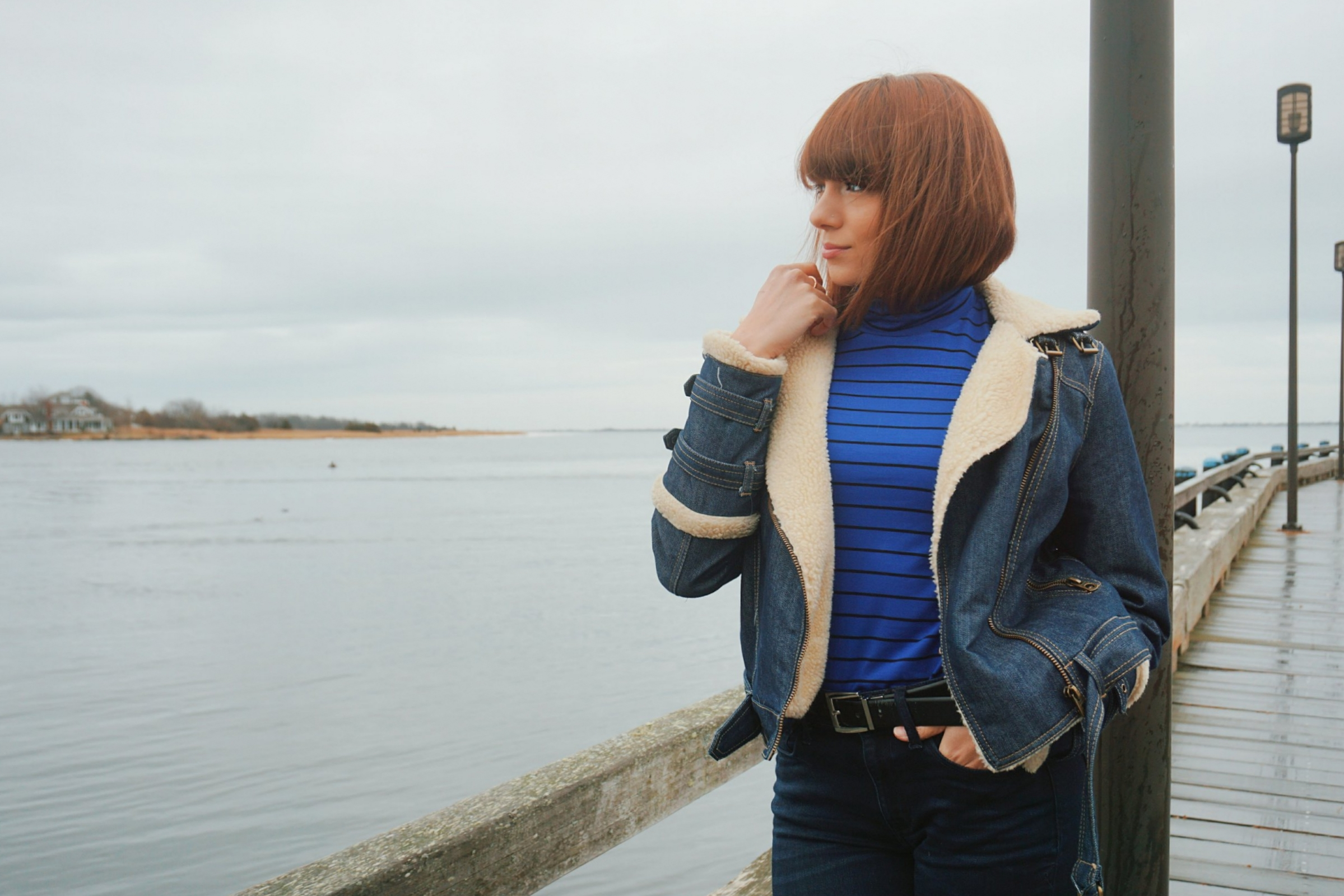 A blogger looking at the ocean, and wearing winter denim jacket, blue turtleneck, and jeans.