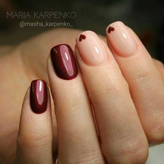 Beautiful nail art: dark red and nude with little hearts.