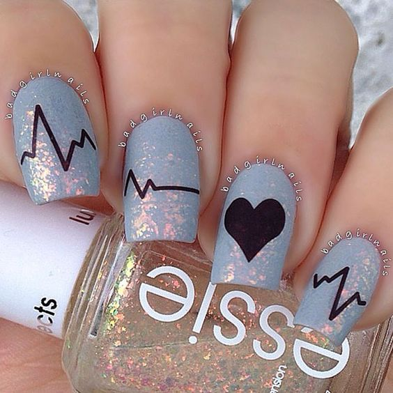 Beautiful blue nail polish, and heart rate design on nails.