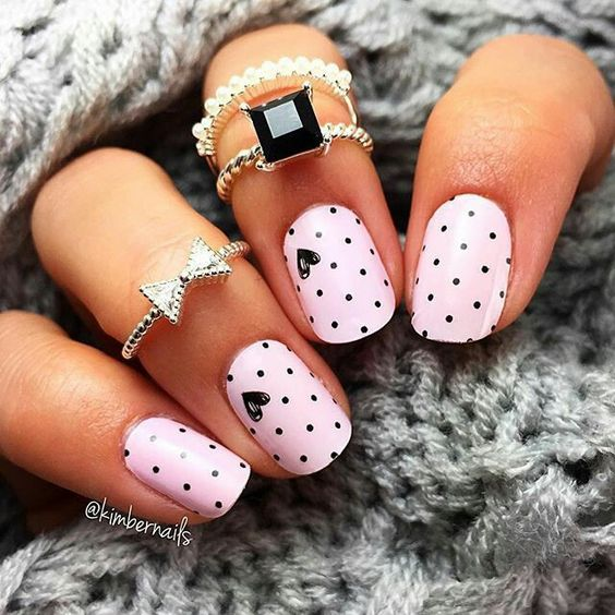 Pink nails with black polka dots on the nails.
