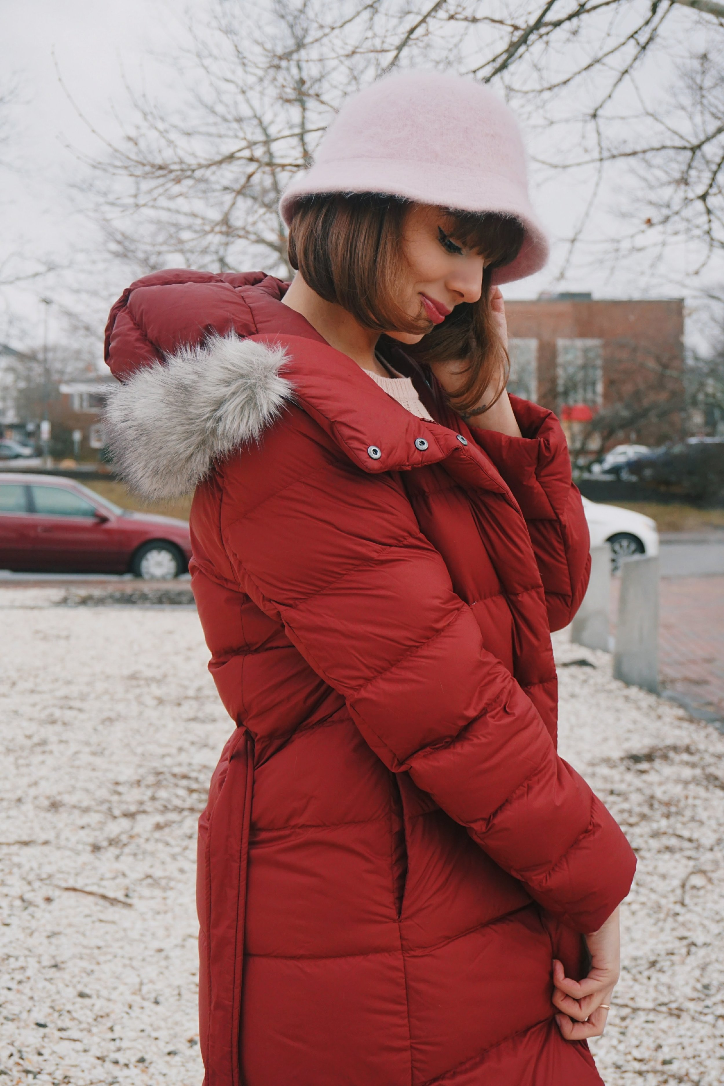 A girl looking down on the ground; she is wearing a cranberry colour winter coat and a pink hat.