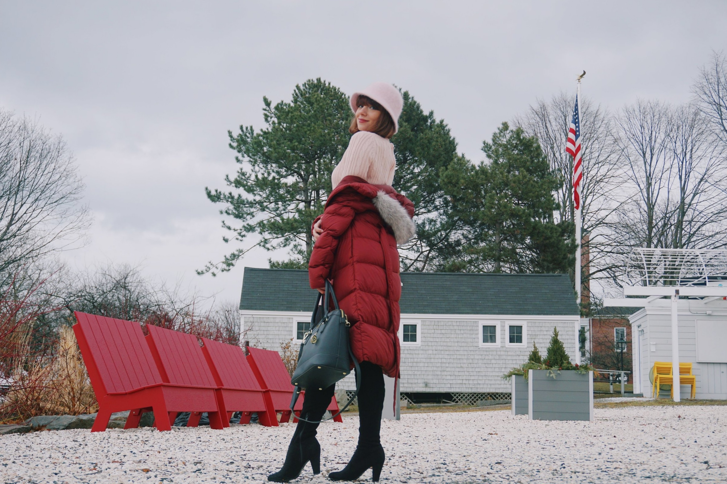 Beauty blogger wearing a puffy winter coat, pink hat, over the knee boots, and black bag.
