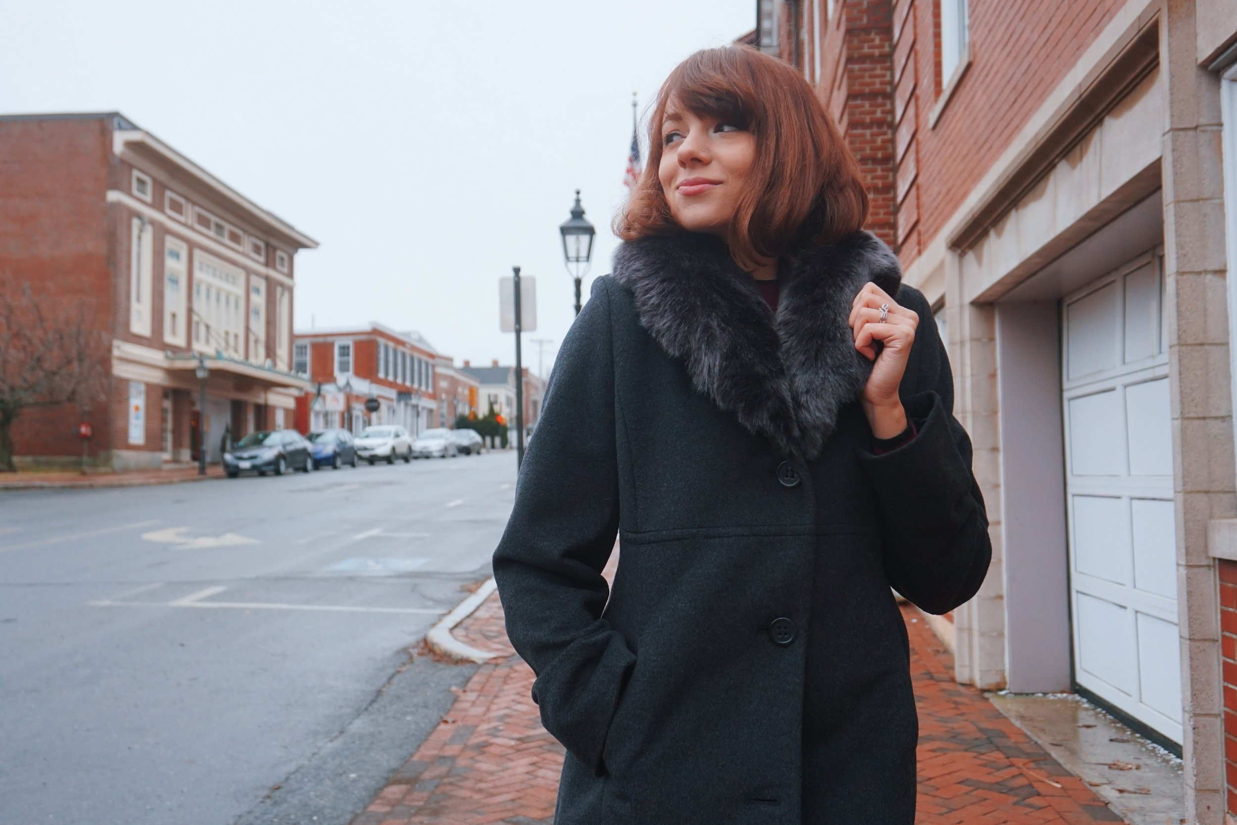 A fashion blogger looking to the side and posing on the street of Newburyport.
