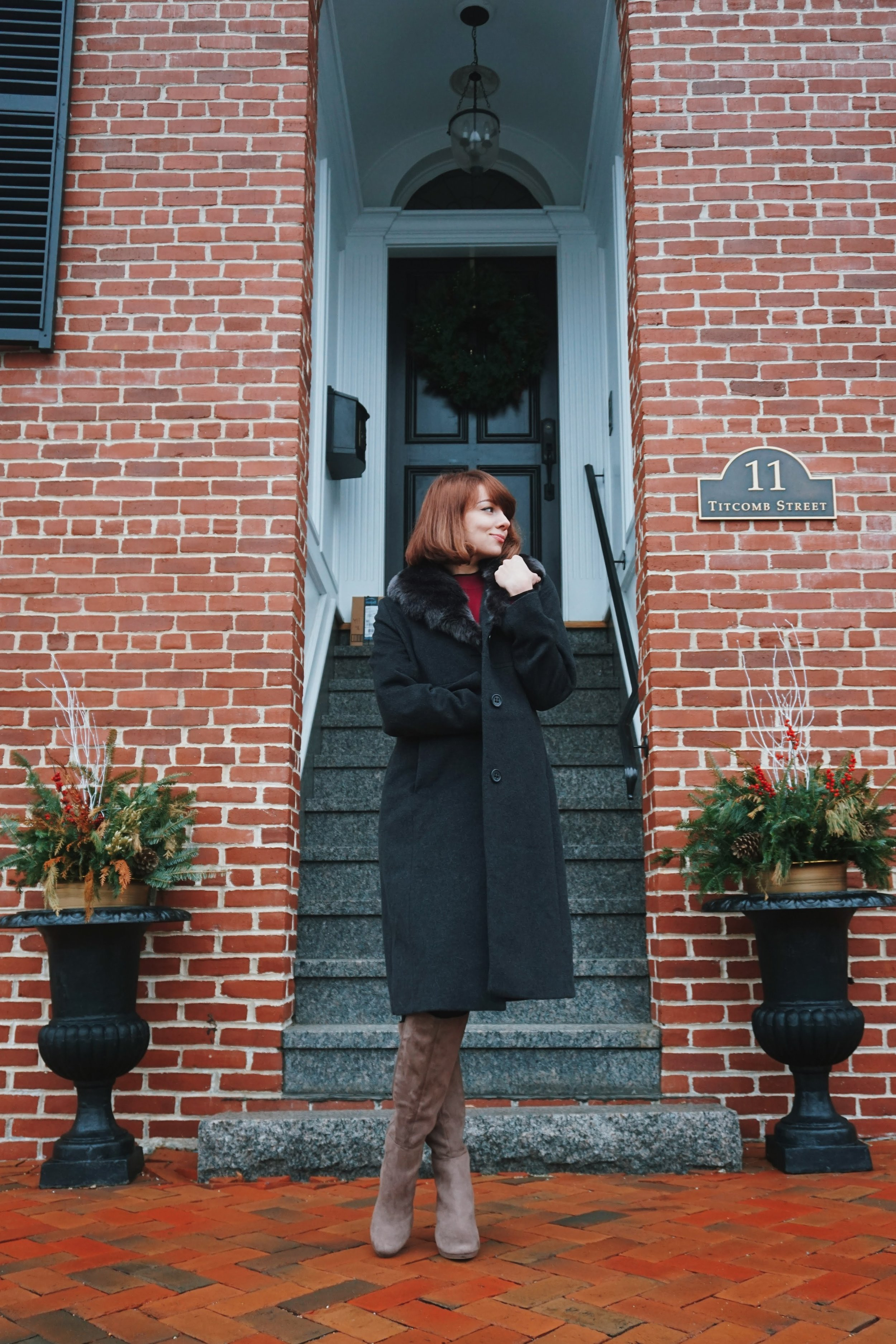A blogger posing next to a red brick building, wearing a gray coat, light brown boots, and maroon colour dress.