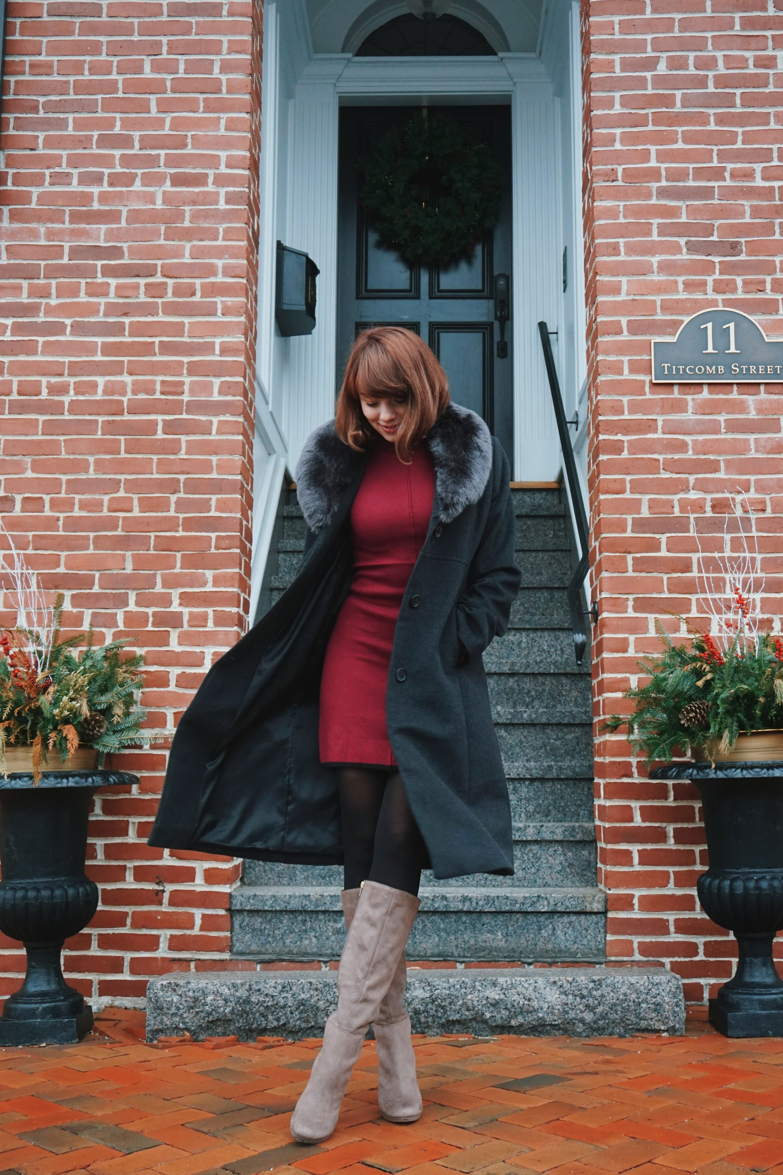 A girl posing next to a brick building, wearing an elegant winter outfit.
