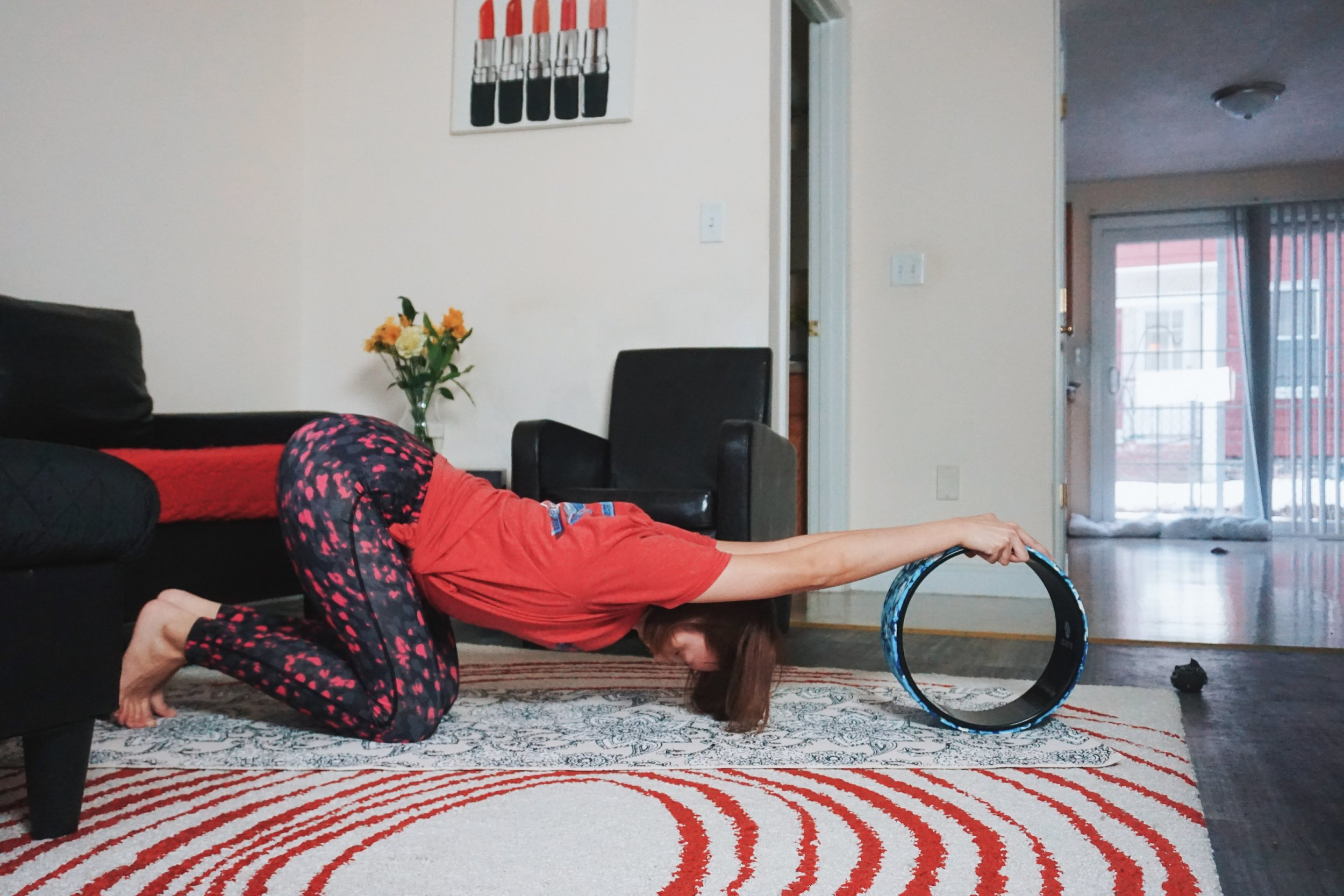 A beginner yogi stretching her chest and shoulders on a yoga wheel.