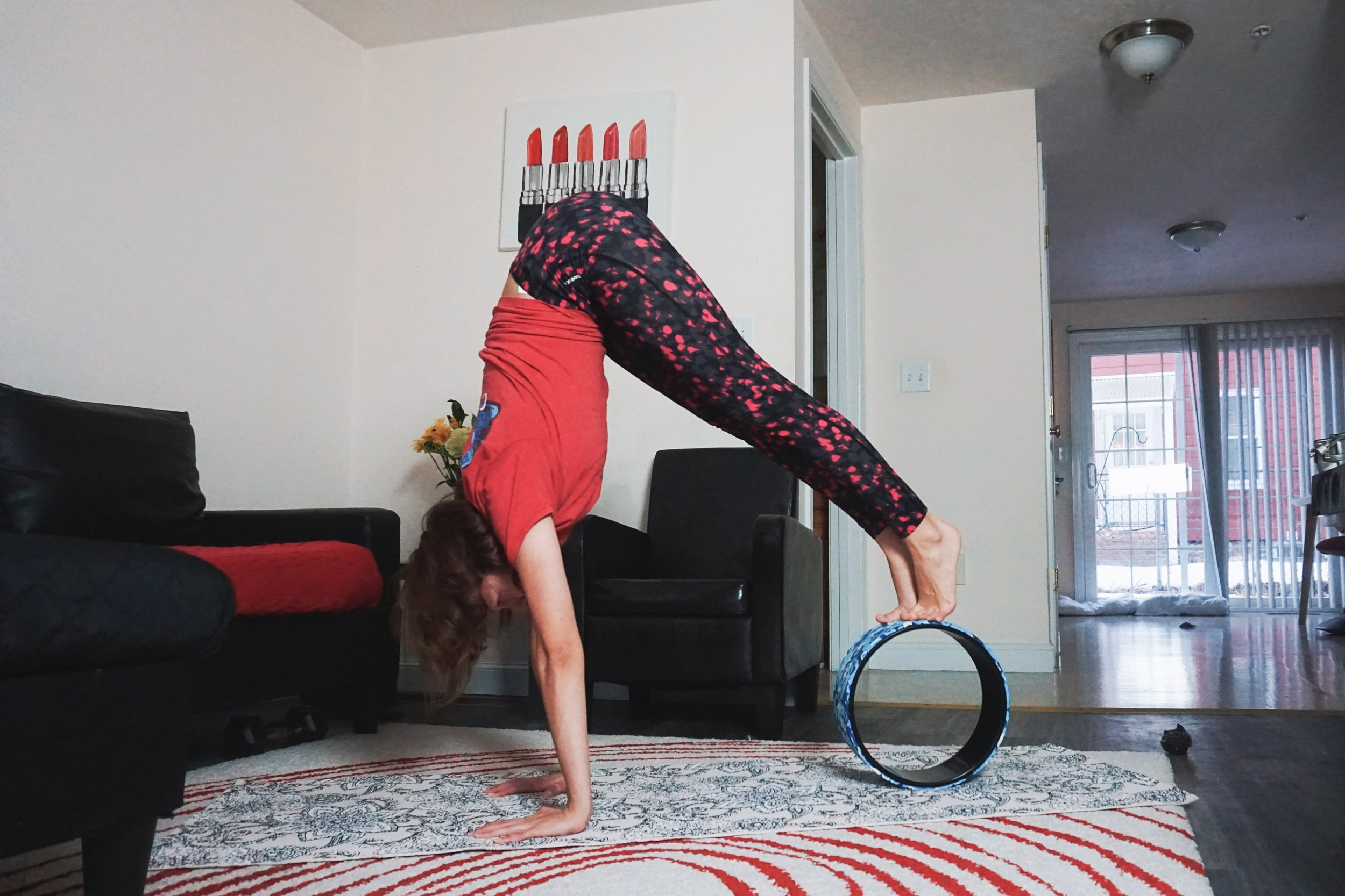 A blogger is showing how to use a yoga wheel to do a handstand.
