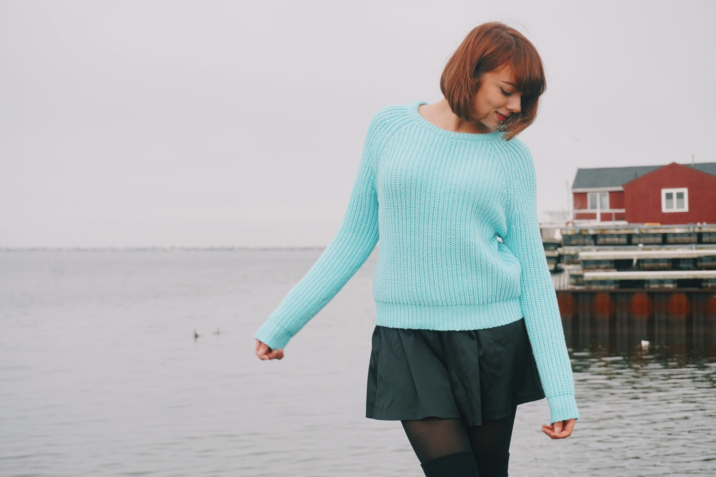 A blogger looking down in the photo. She is wearing a blue knitted sweater, black skirt, black tights and over the knee socks.