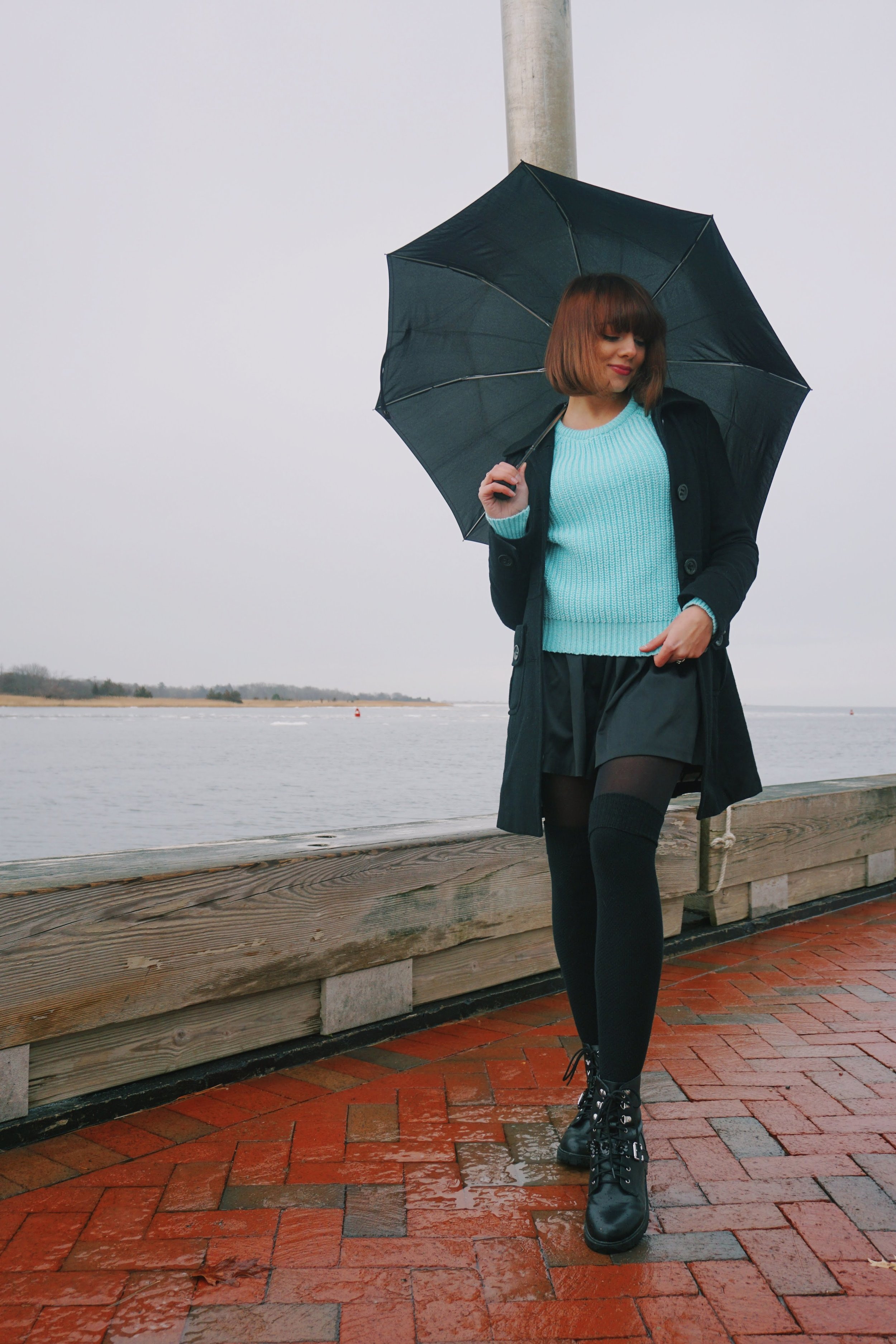 Girl posing near the ocean, wearing a cute winter outfit.
