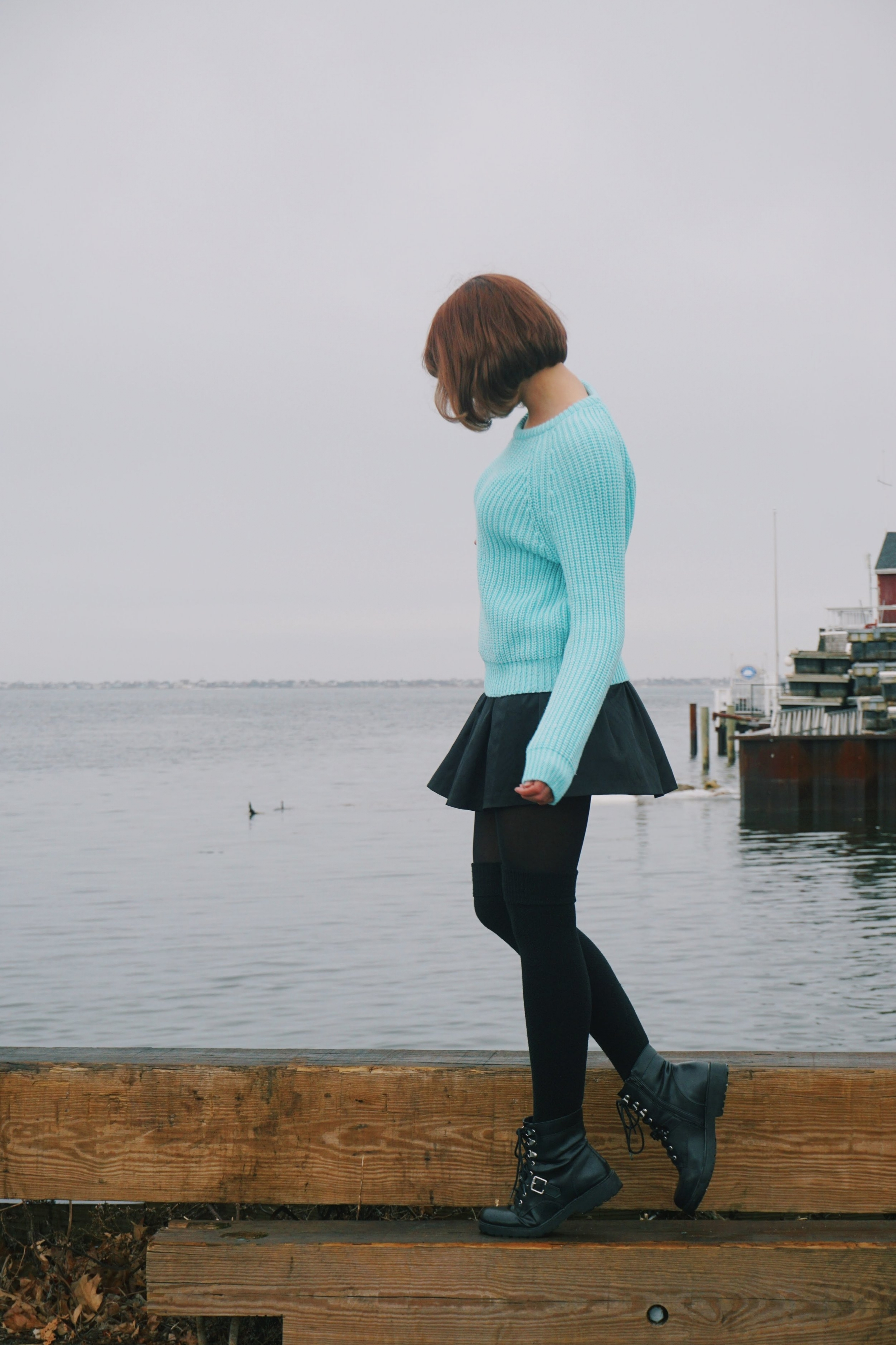 A photo of a girl standing near the ocean, looking down on her feet. She is wearing a blue sweater, short black skirt, black tights and over the knee socks, and black army-style boots.