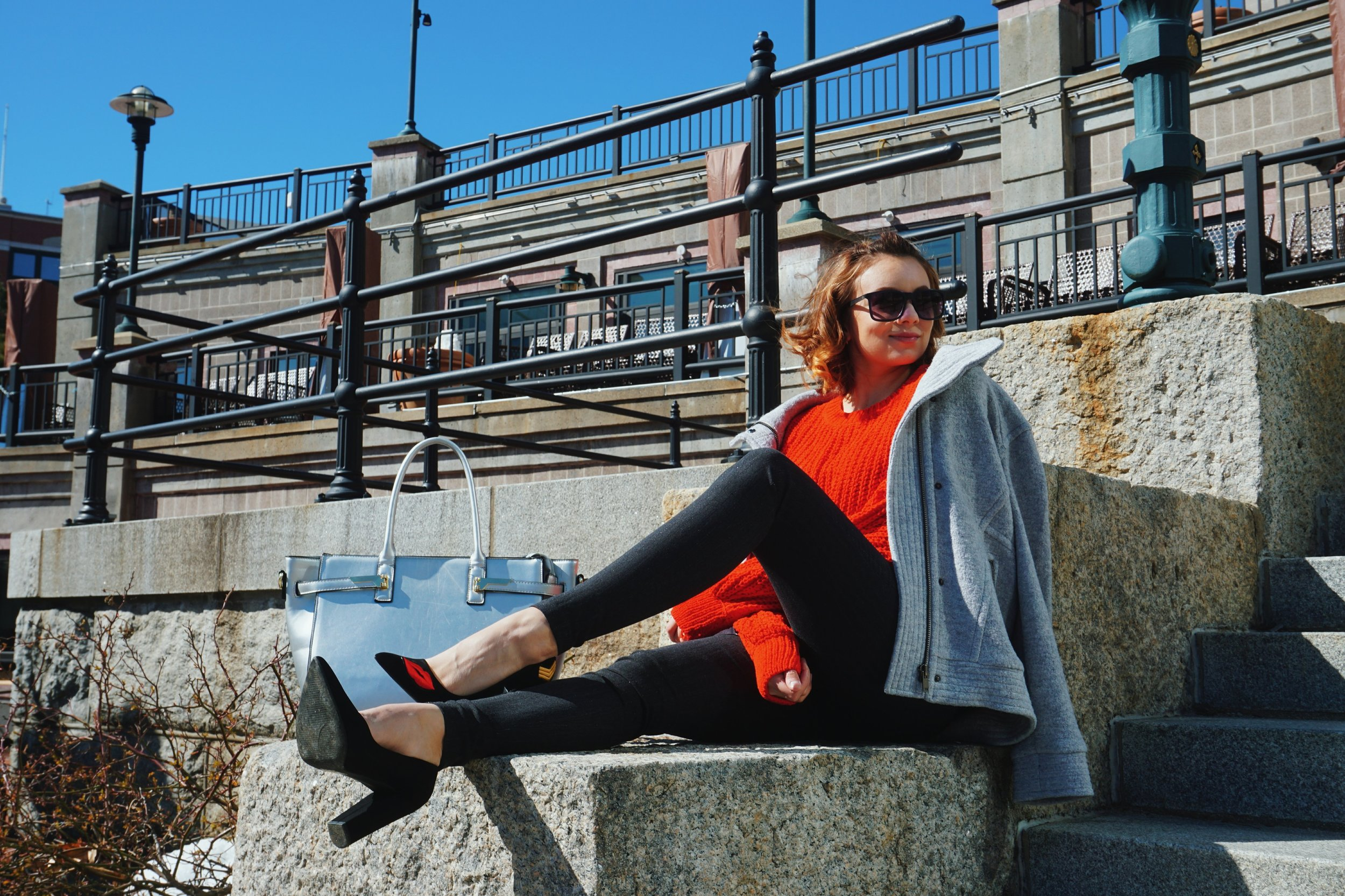 A girl sitting on concrete steps, wearing a red chunky sweater, gray coat, gray pants, and black pumps.