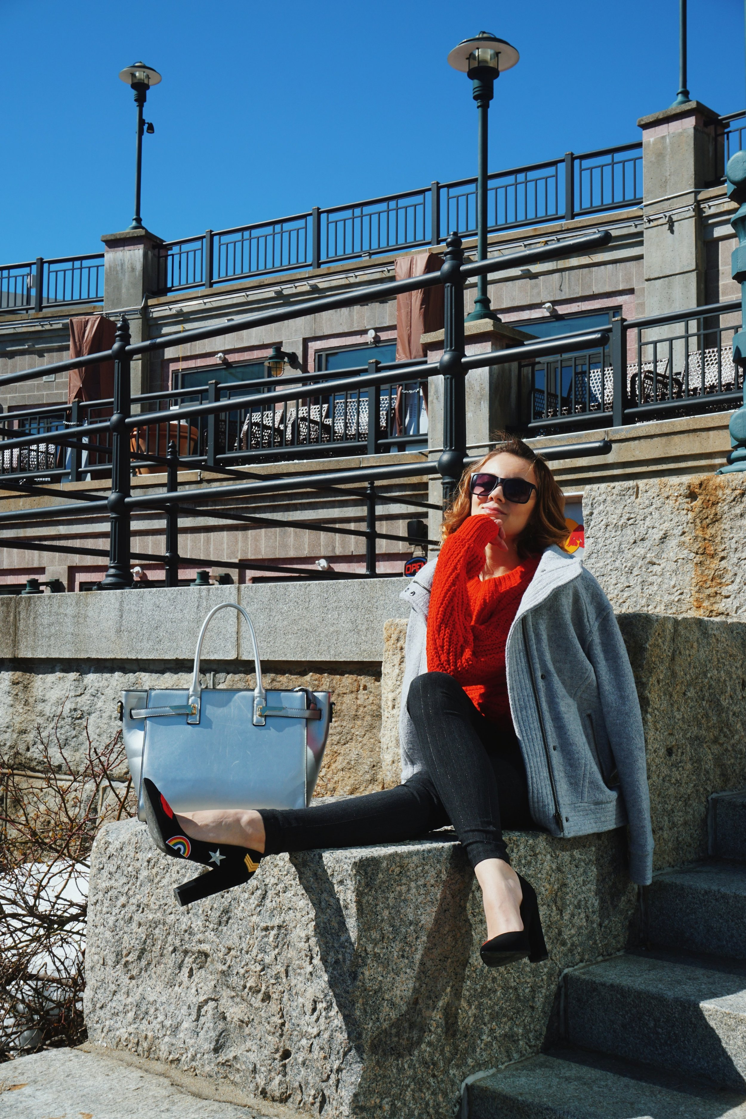 Fashion outfit inspiration on a blogger: red chunky sweater, skinny dark pants, black pumps, gray coat hanging off the shoulder, and silver bag.