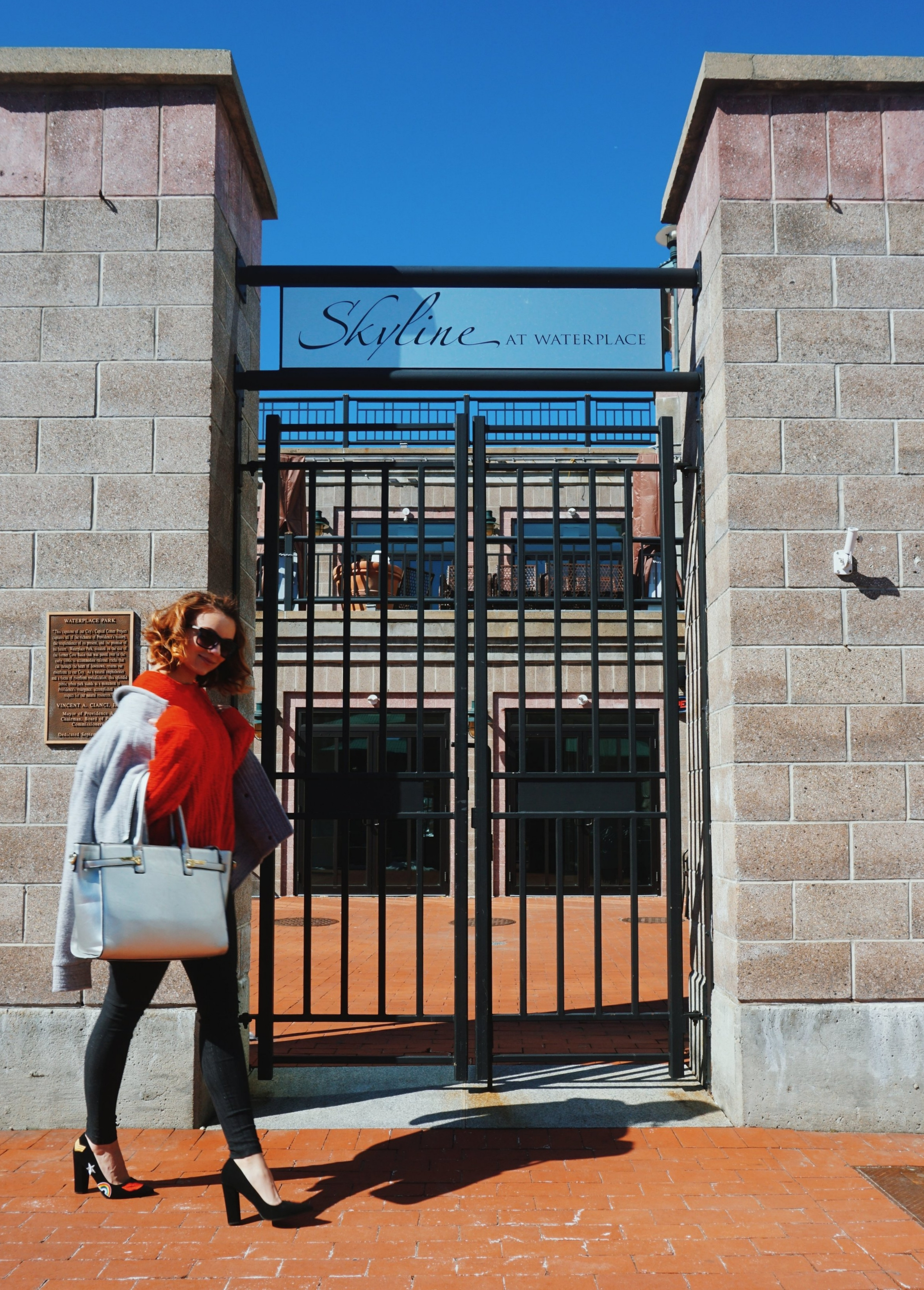 Blogger walking by the gates of an outside restaurant, wearing dark pants, black pumps with fun design on them, red sweater, gray coat, and silver bag.